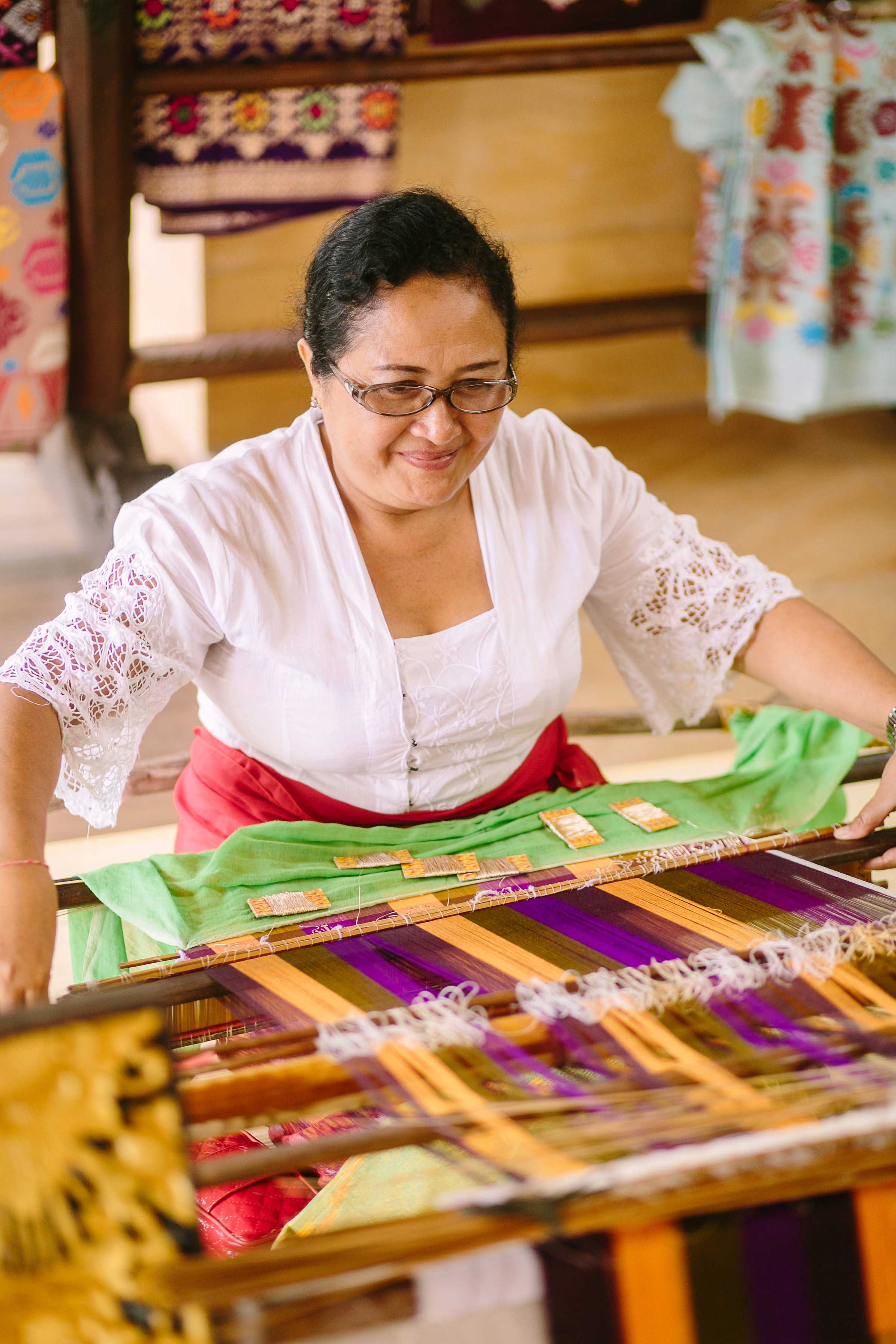 Woman making textiles on loom at The Mulia Resort in Bali Marry at the Mulia event