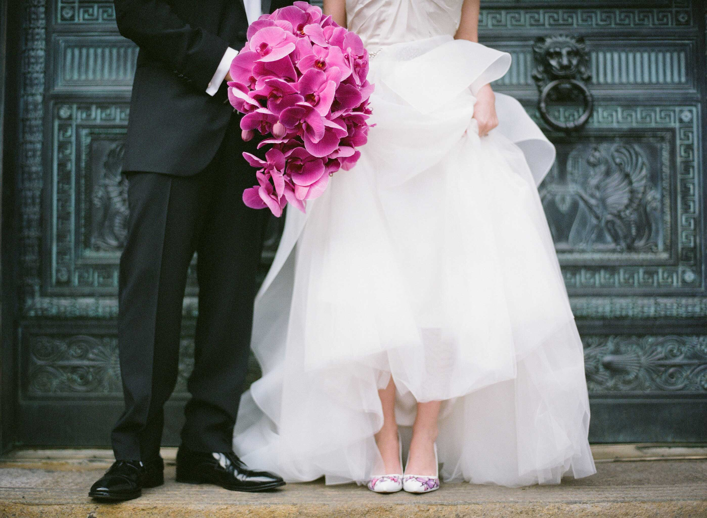 Bride in voluminous wedding dress with handpainted heels and fuchsia orchid bouquet