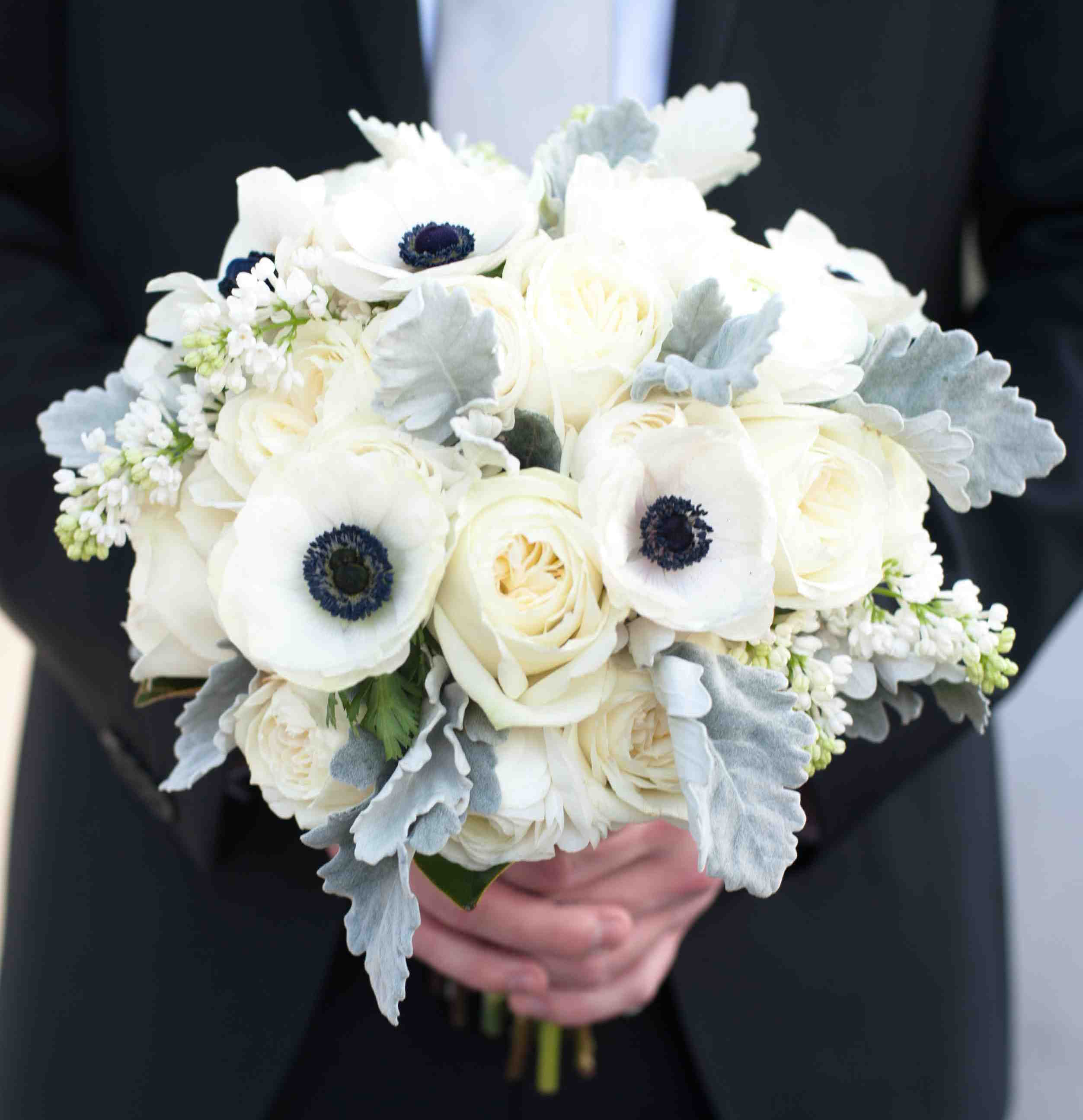 Groom holding white bouquet with anemone flower and dusty miller