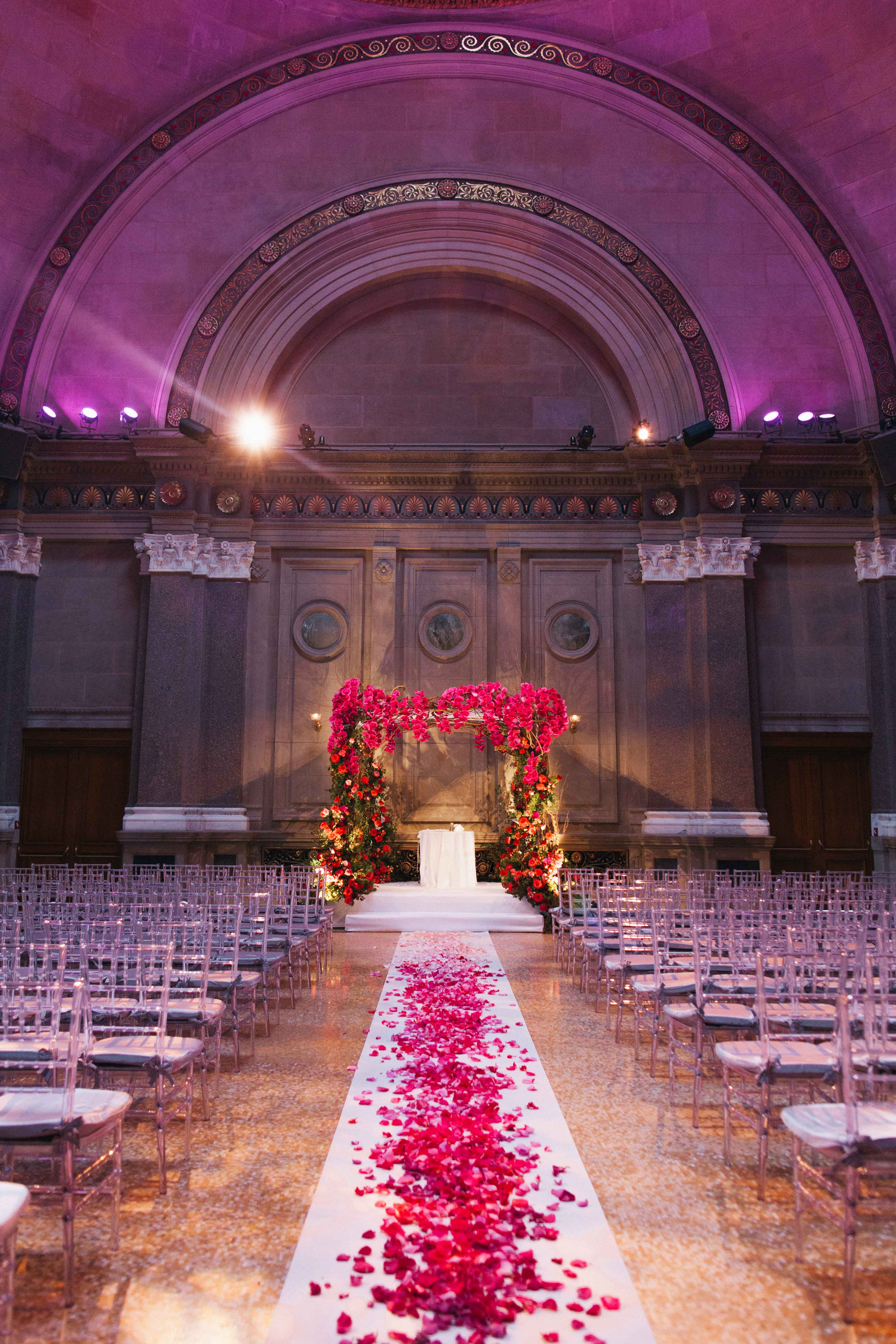 Fuchsia lighting at wedding ceremony with orchid chuppah