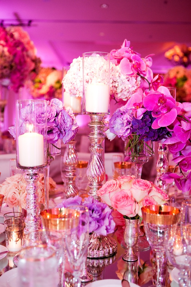 Bright fuchsia lighting at luxe wedding reception