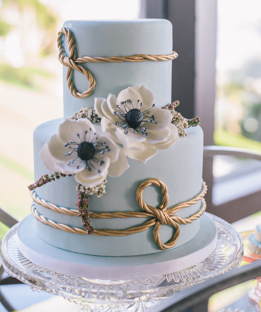 Blue two layer wedding cake with gold rope white anemone flowers