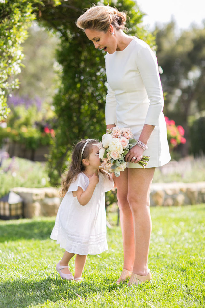 Bride in short white wedding dress long sleeves with flower girl smelling bouquet