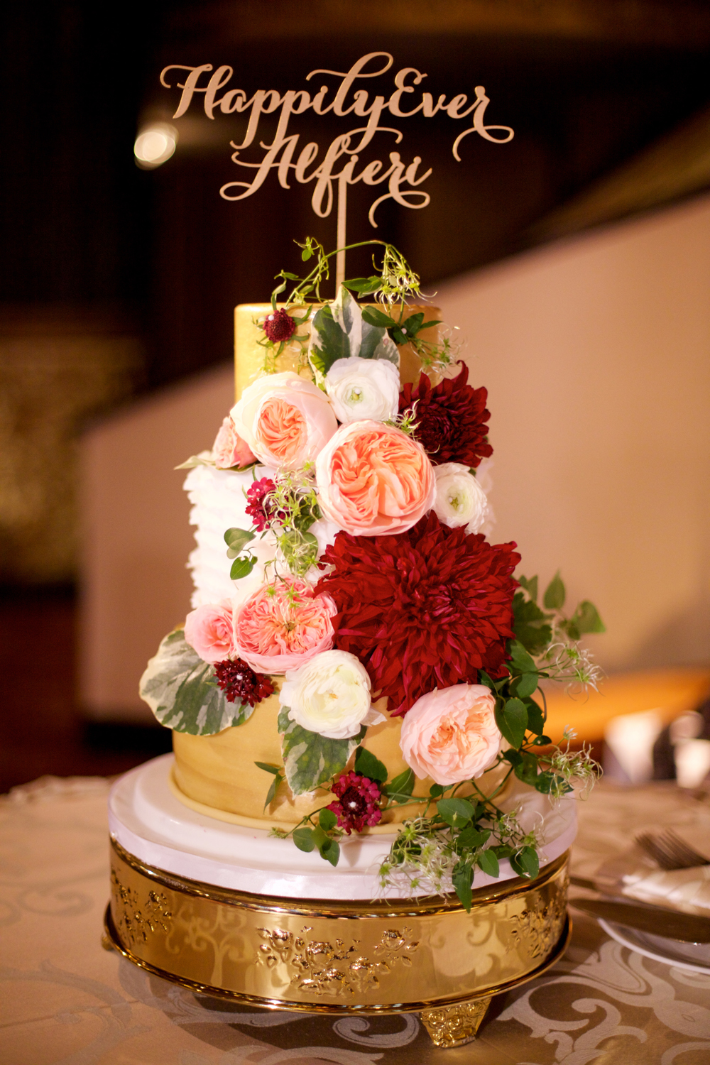 fall wedding cake with fresh flowers, garden roses, red dahlias, gold layer