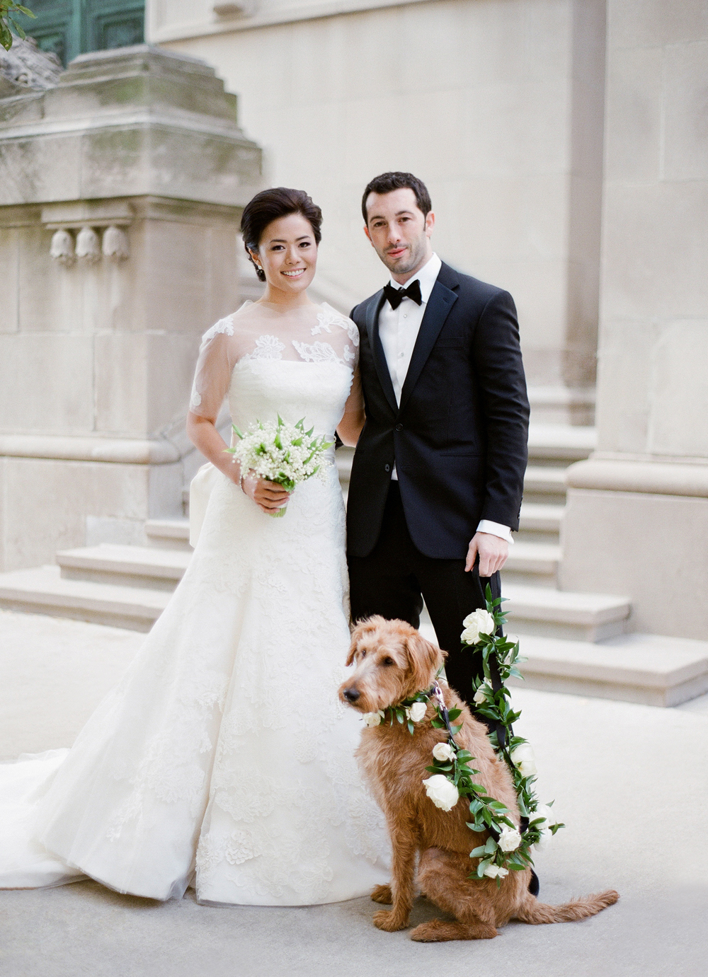 bride in vera wang and groom in ralph lauren stand with dog ring bearer on garland leash