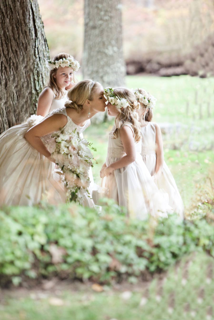 Bride in forest kissing flower girls on forehead