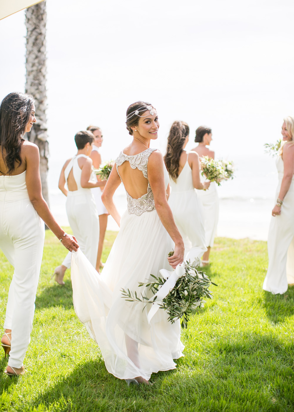 bride in jenny packham with keyhole back and headpiece, bridesmaids in white jumpsuits