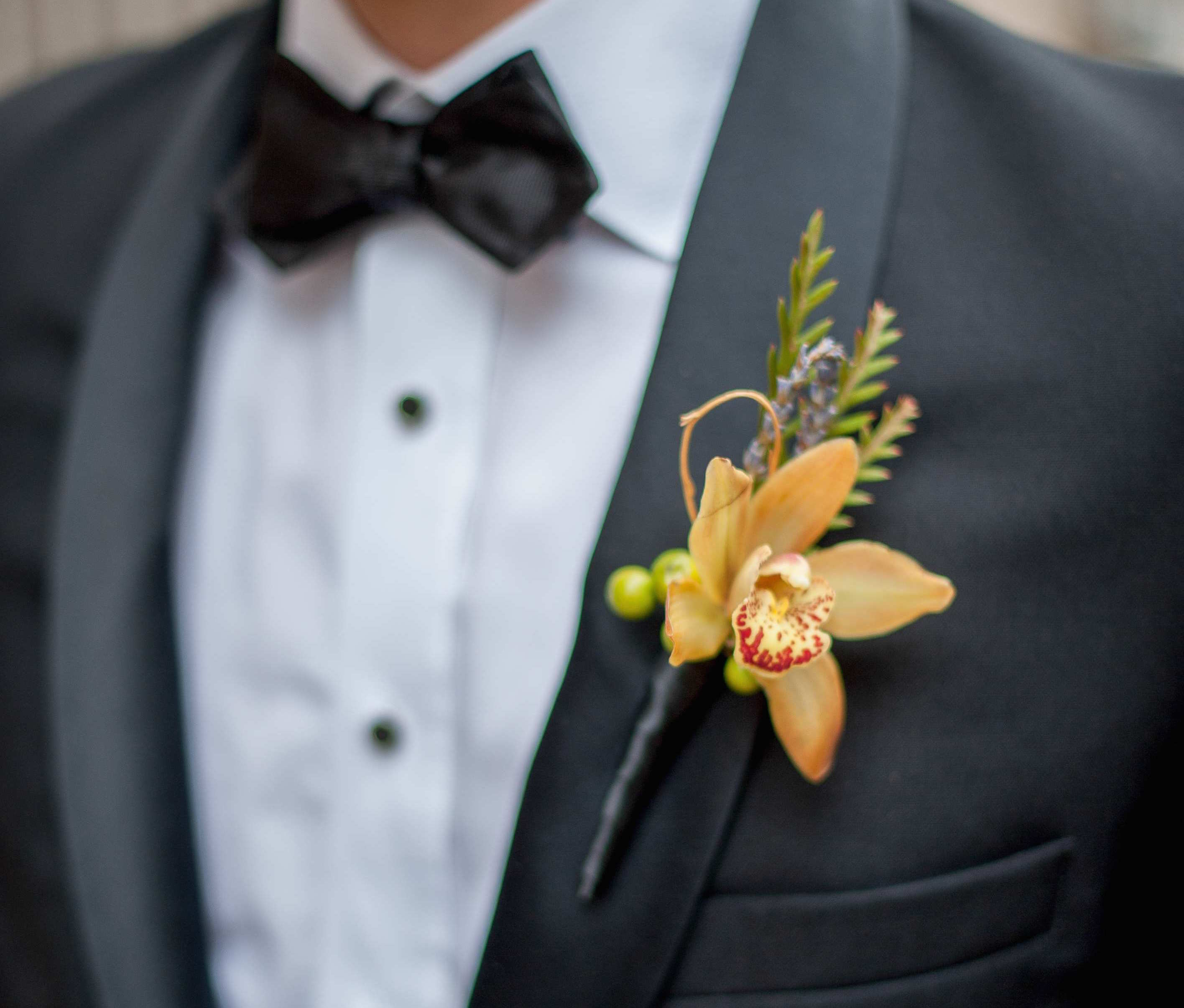 Orange orchid boutonniere for fall wedding
