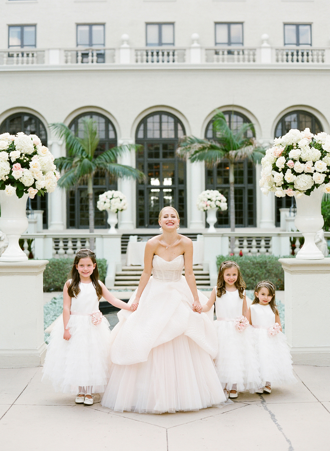 Bride in blush strapless ball gown with flower girls at The Breakers