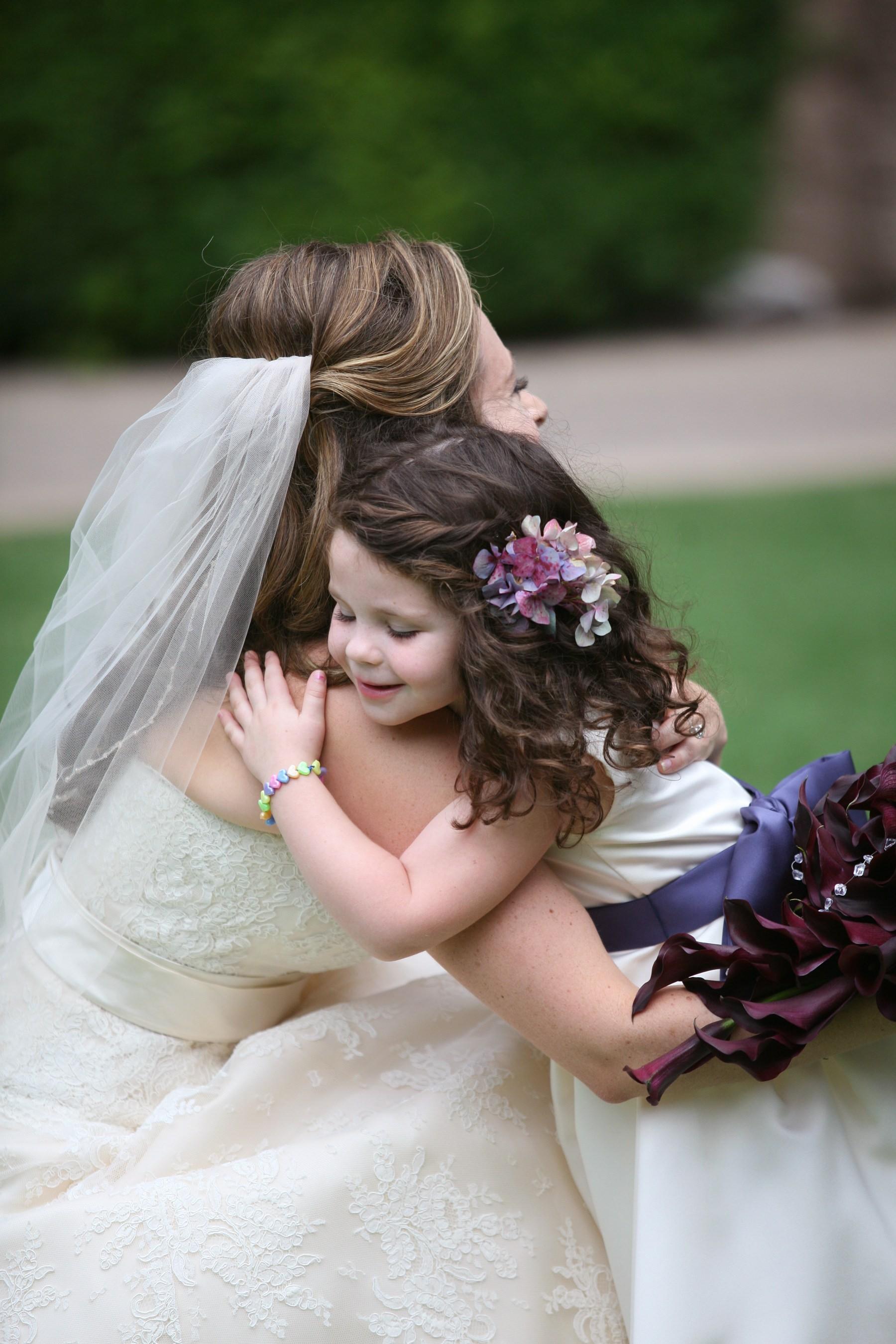 Little flower girl in white dress purple bow hugging bride