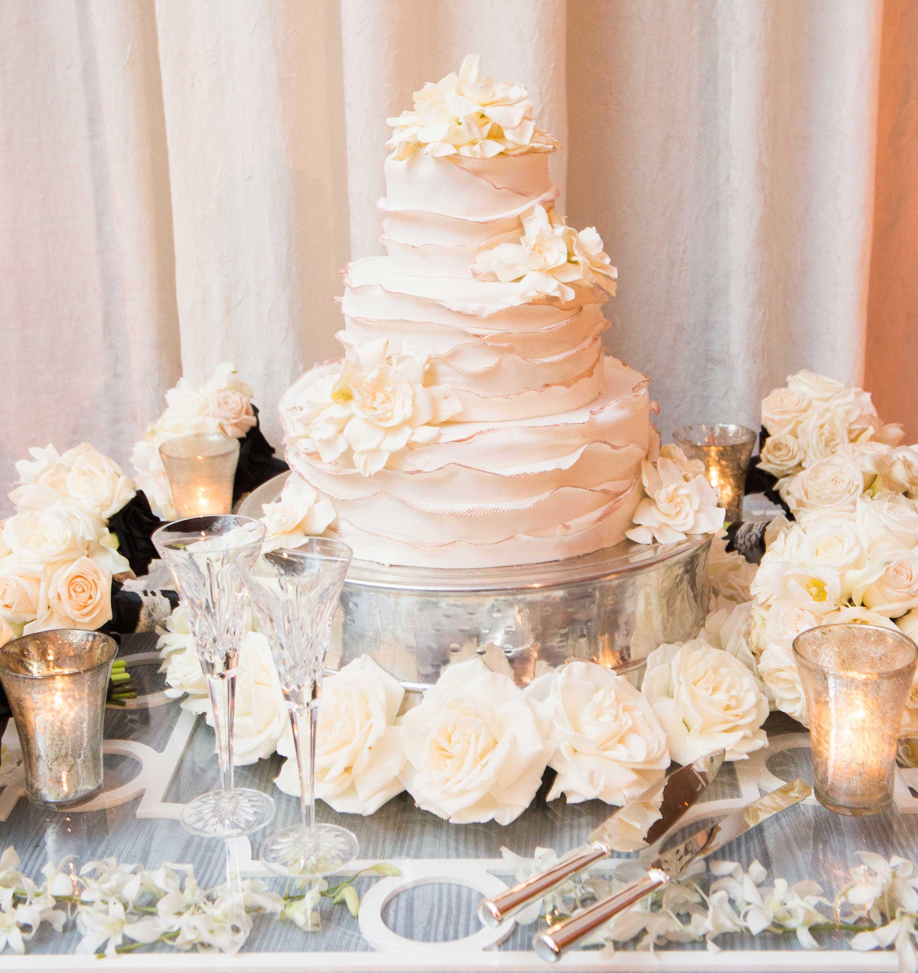 White wedding cake with ruffles and sugar flowers