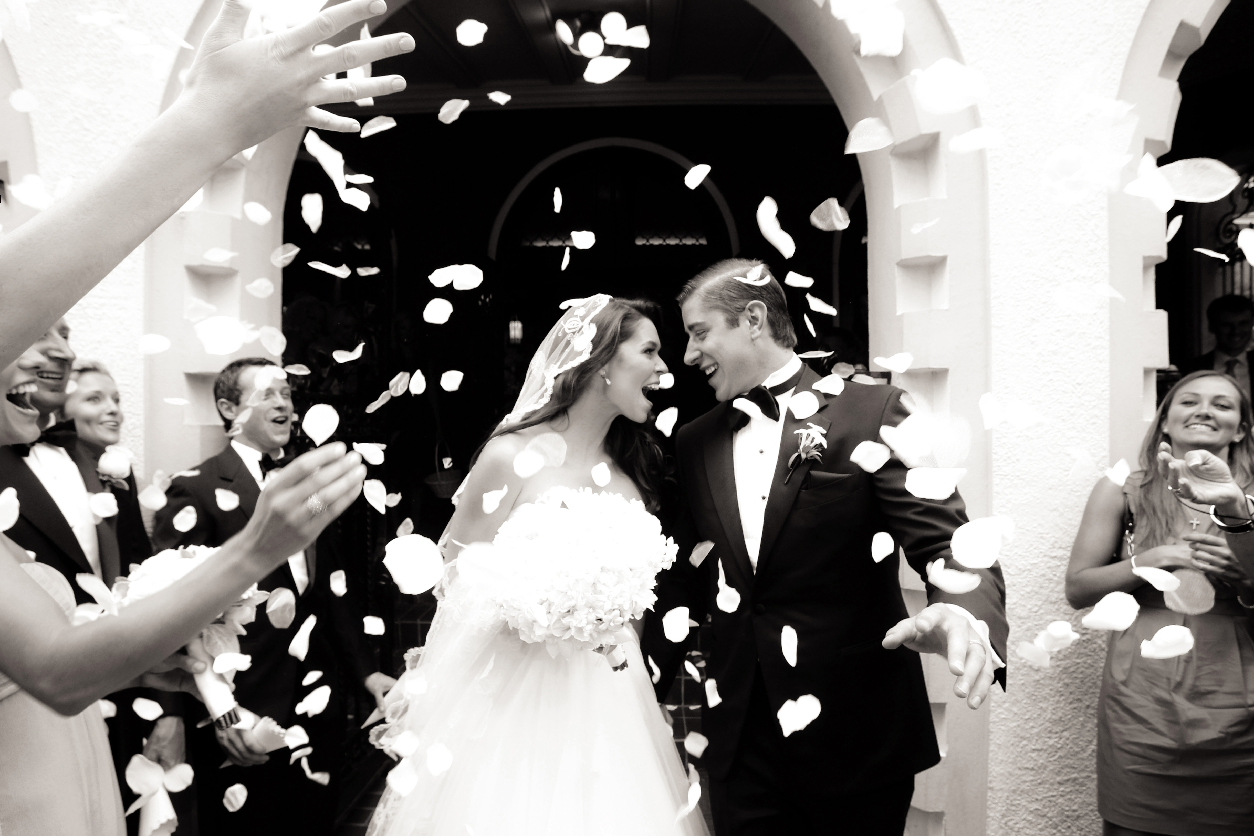 Black and white photo of couple flower petal toss after church wedding