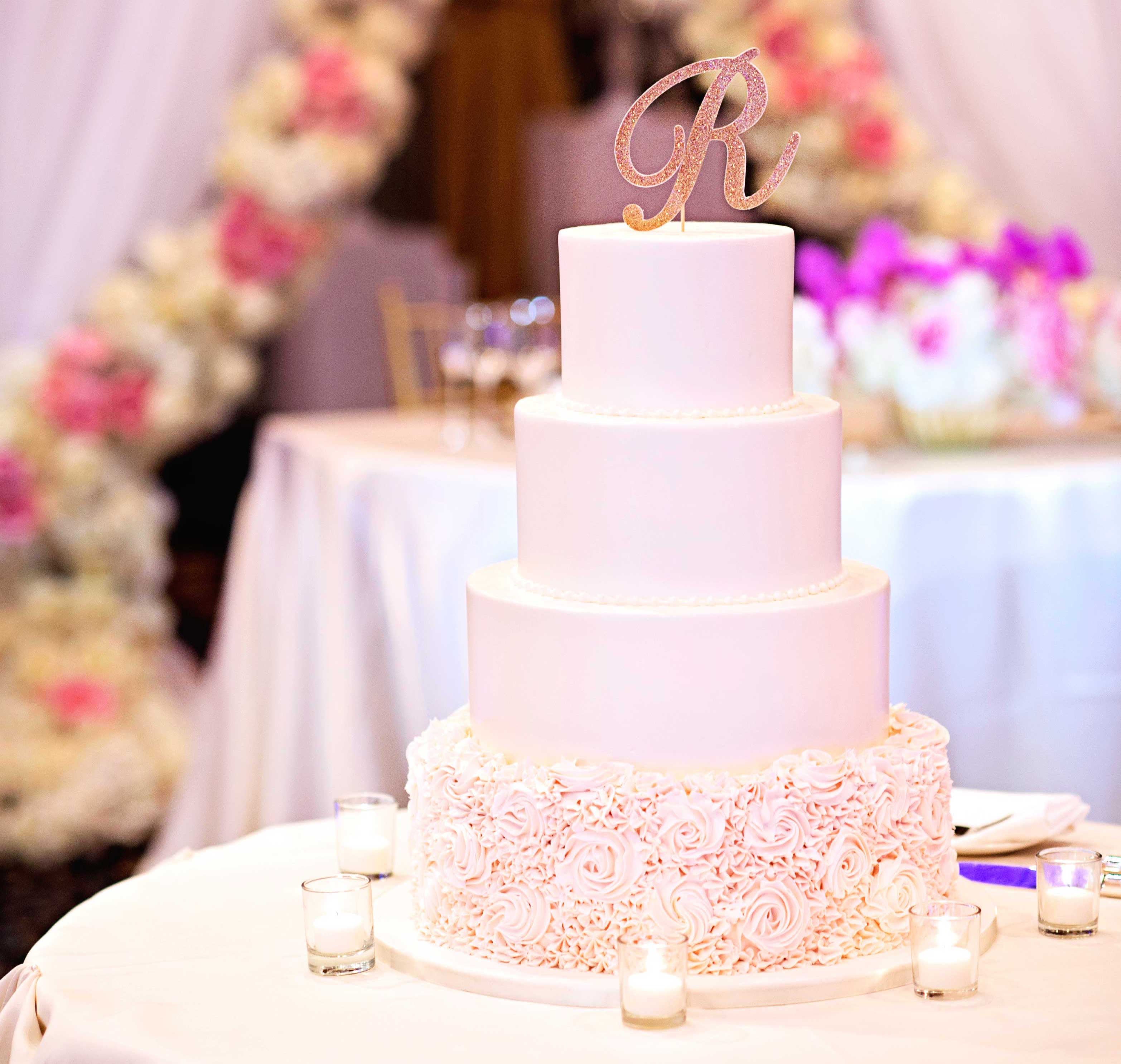 White wedding cake with flower design on bottom layer