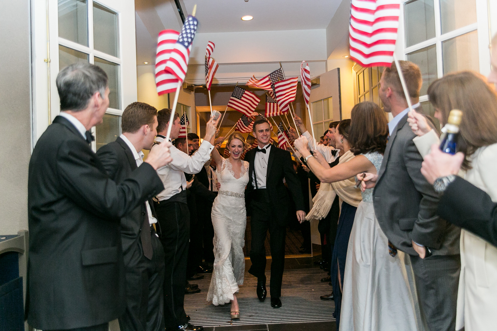 Bride and groom exit guests waving American flags