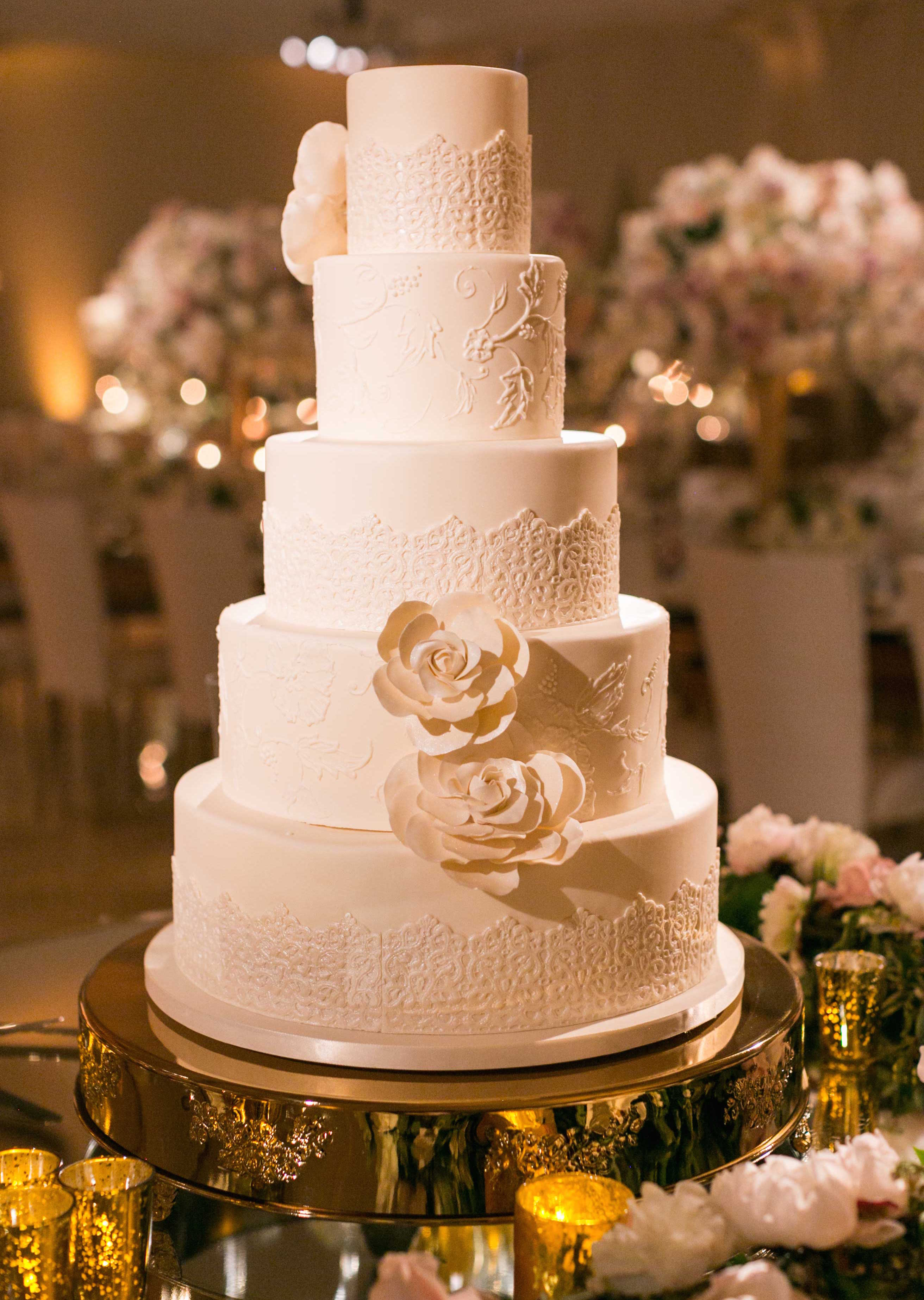 Tall white wedding cake with lace pattern and sugar flowers