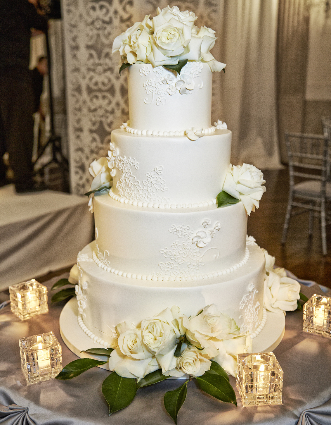 White wedding cake with lace design and fresh flower decorations