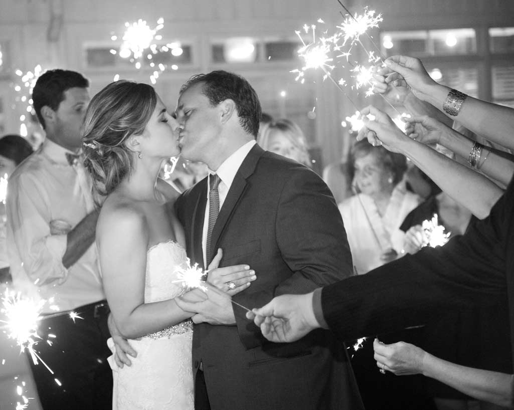 Bride and groom kiss during sparkler exit black and white photo
