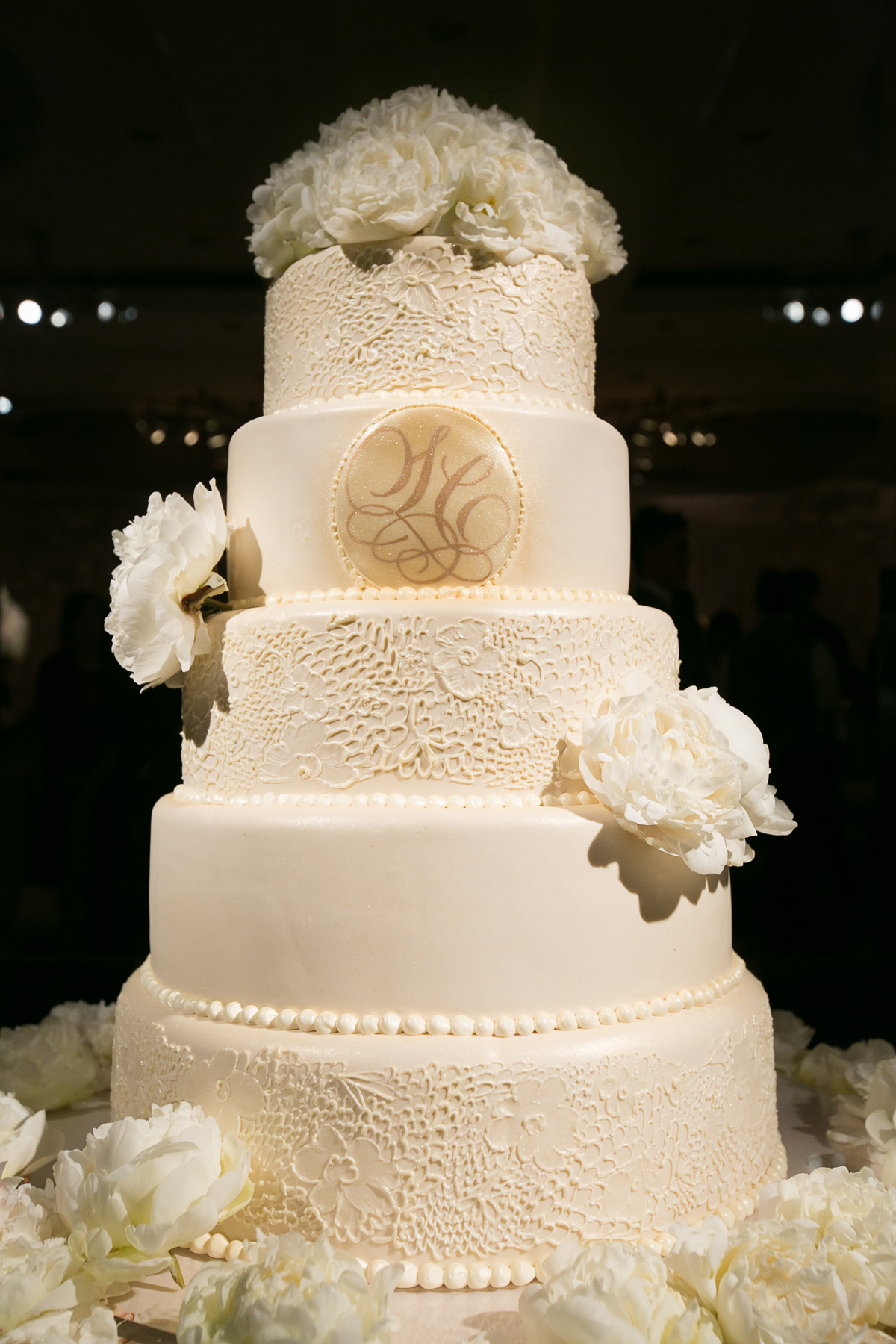 White wedding cake with lace details, monogram, and fresh peony flowers