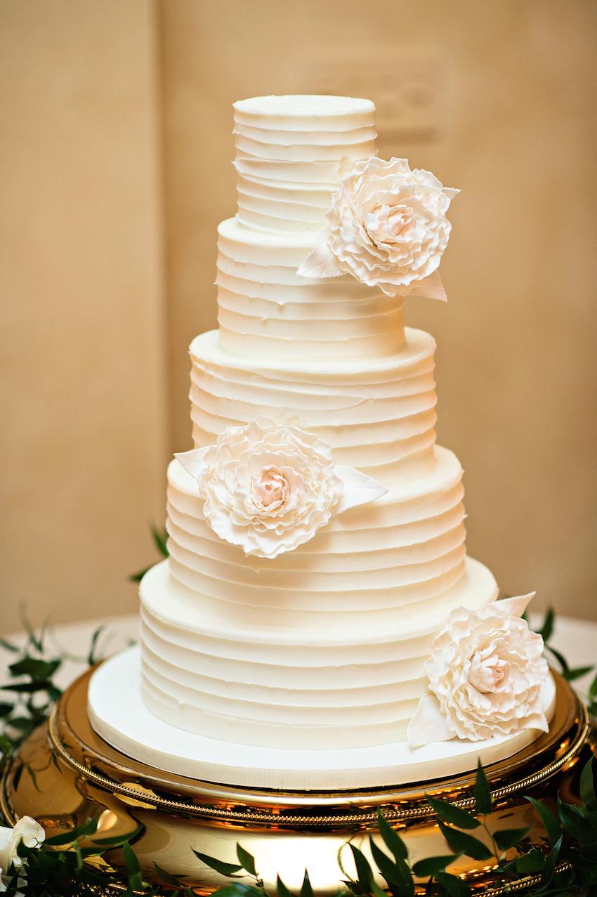 White wedding cake with stripe design and sugar flowers