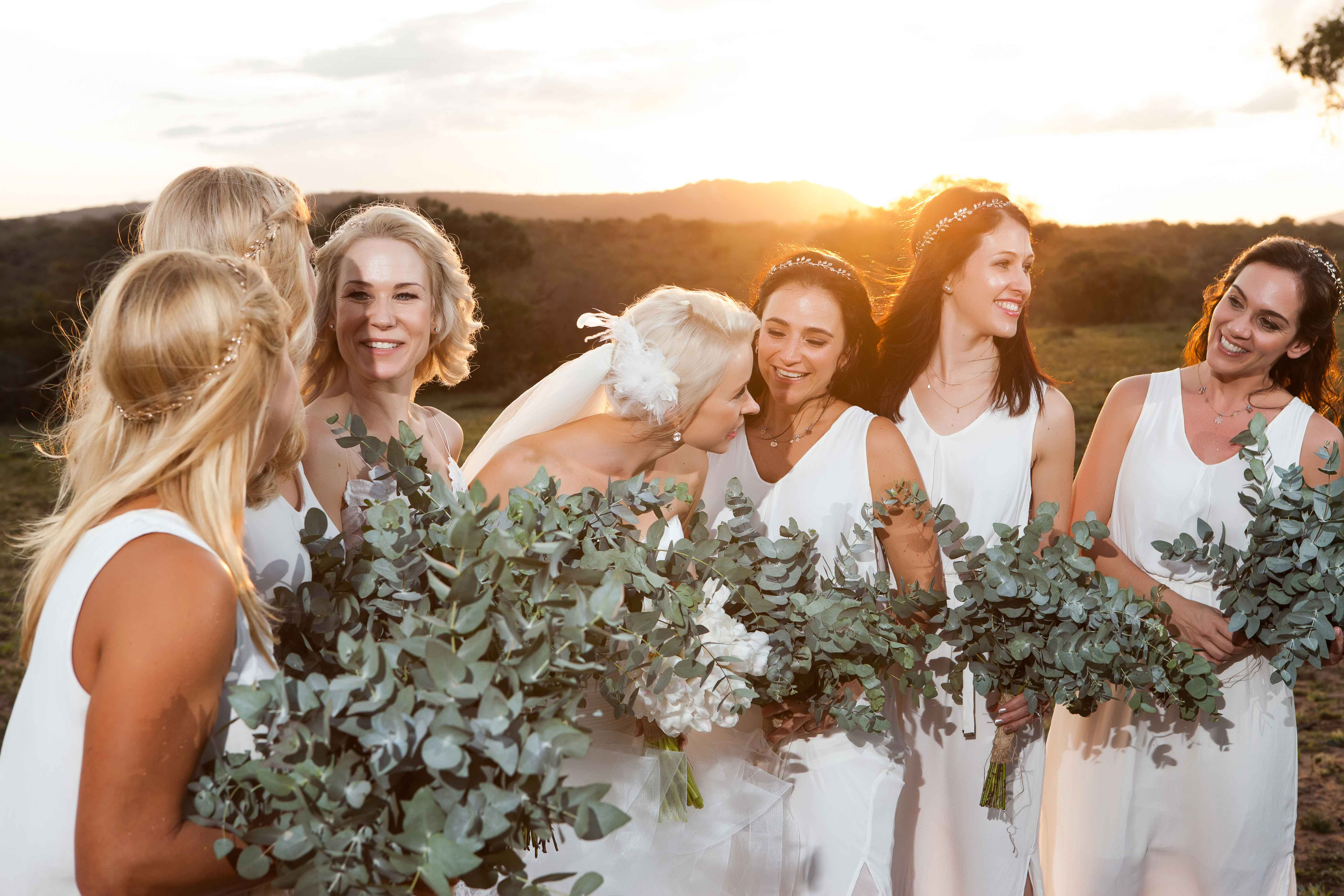 White bridesmaid dresses with leaf greenery bouquets