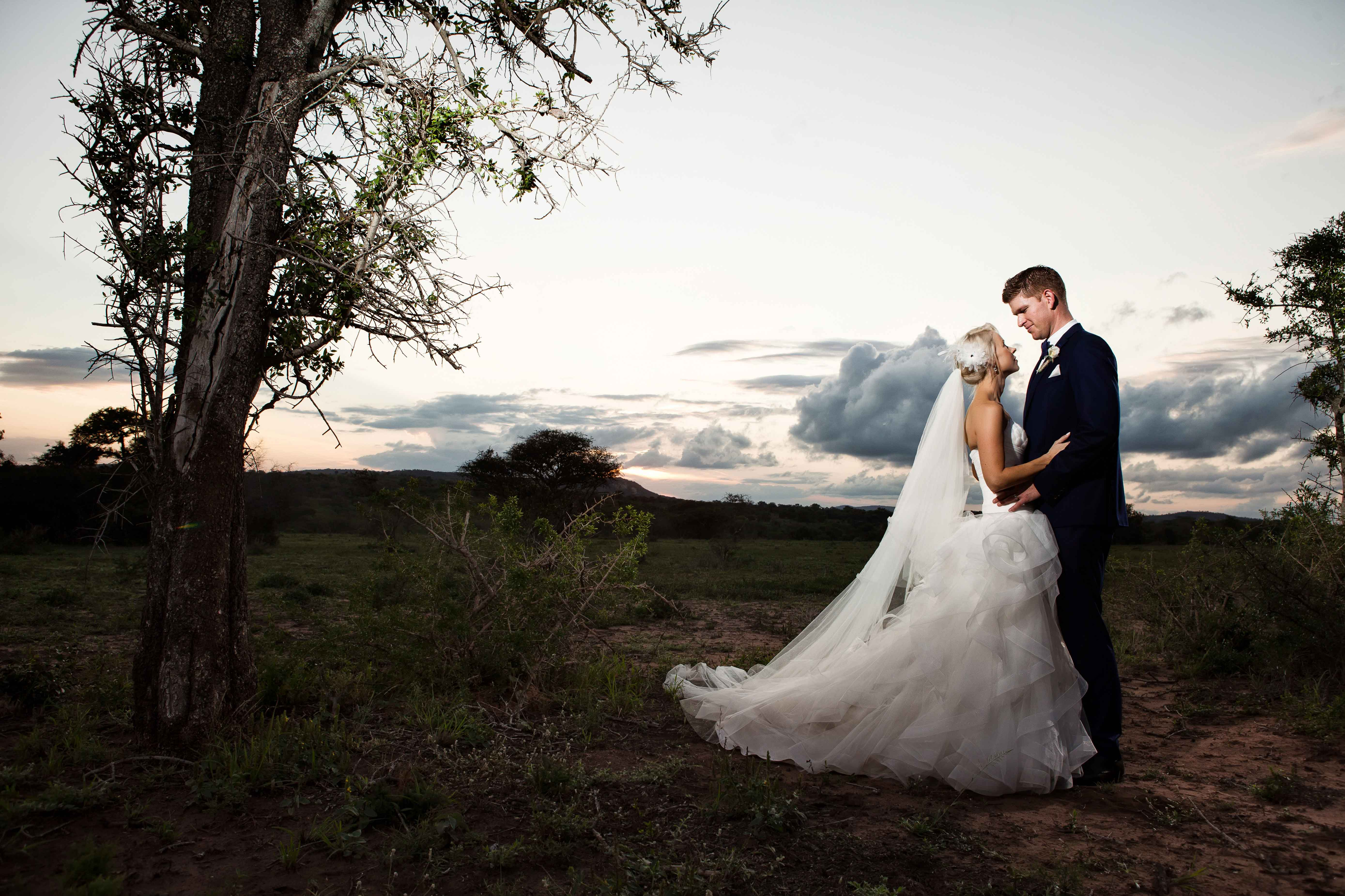 Bridal gown and navy blue suit for groom at sunset