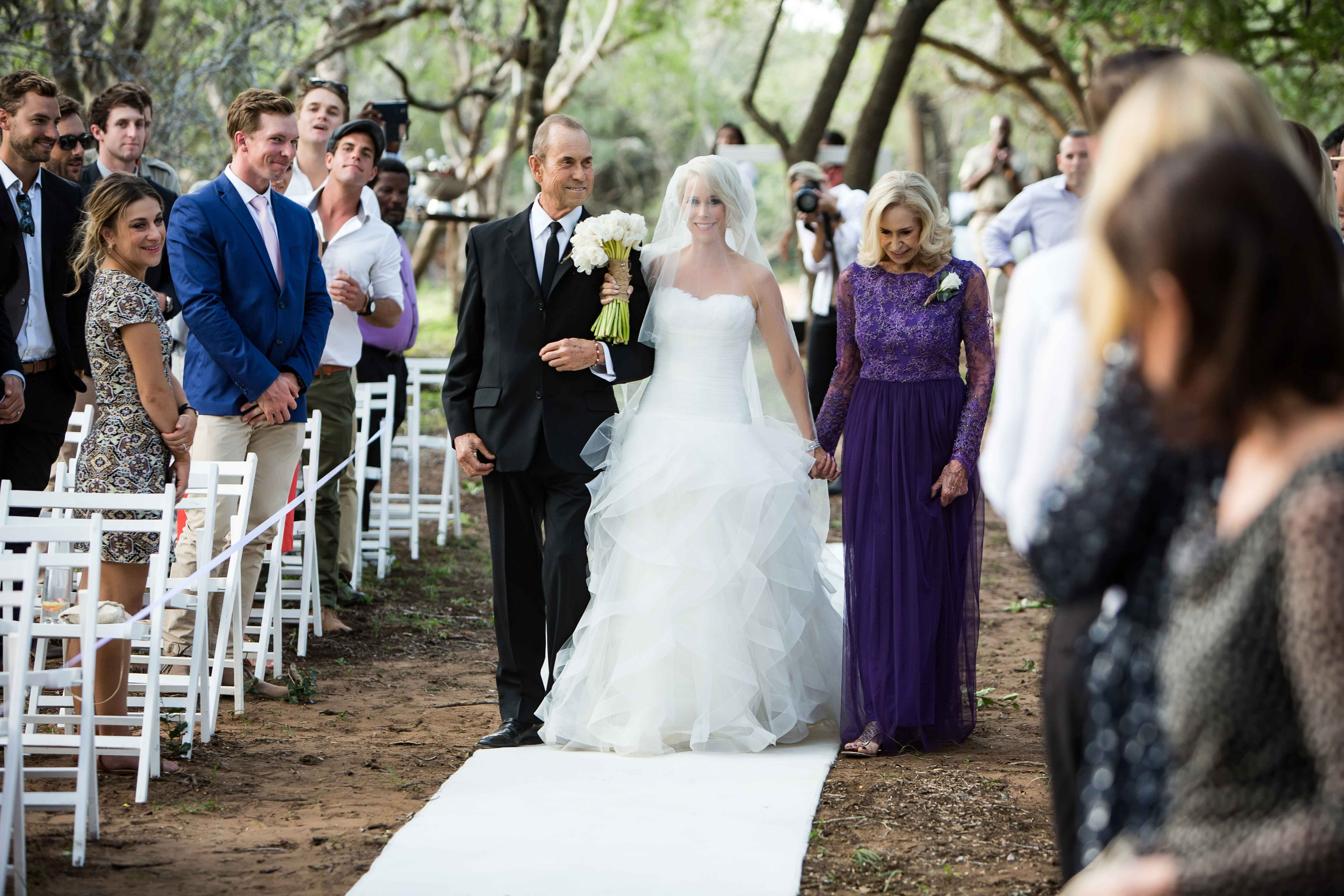 Bride walking down aisle with mother in purple gown and father in tuxedo