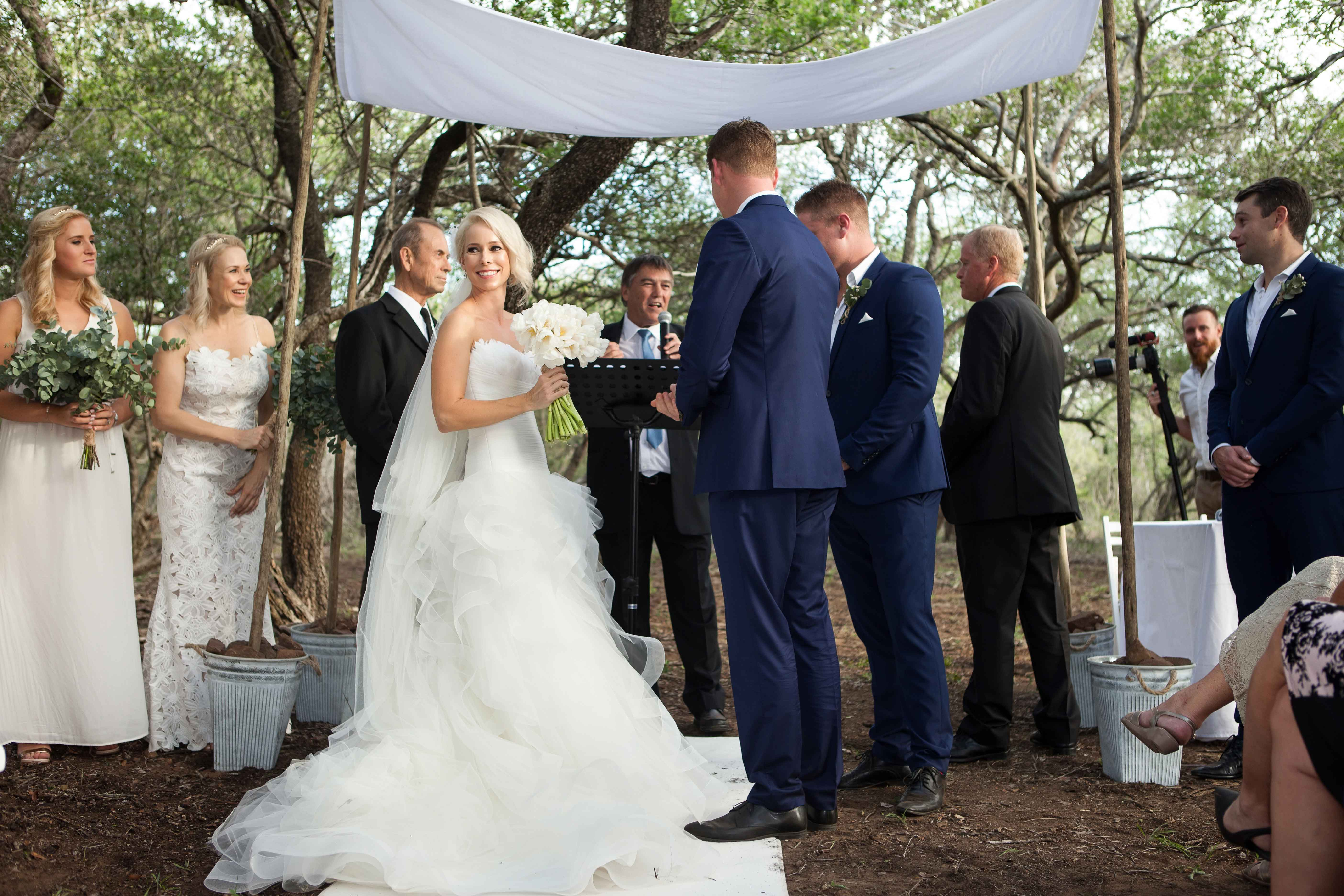Bride holding white bouquet with groom at altar chuppah South Africa