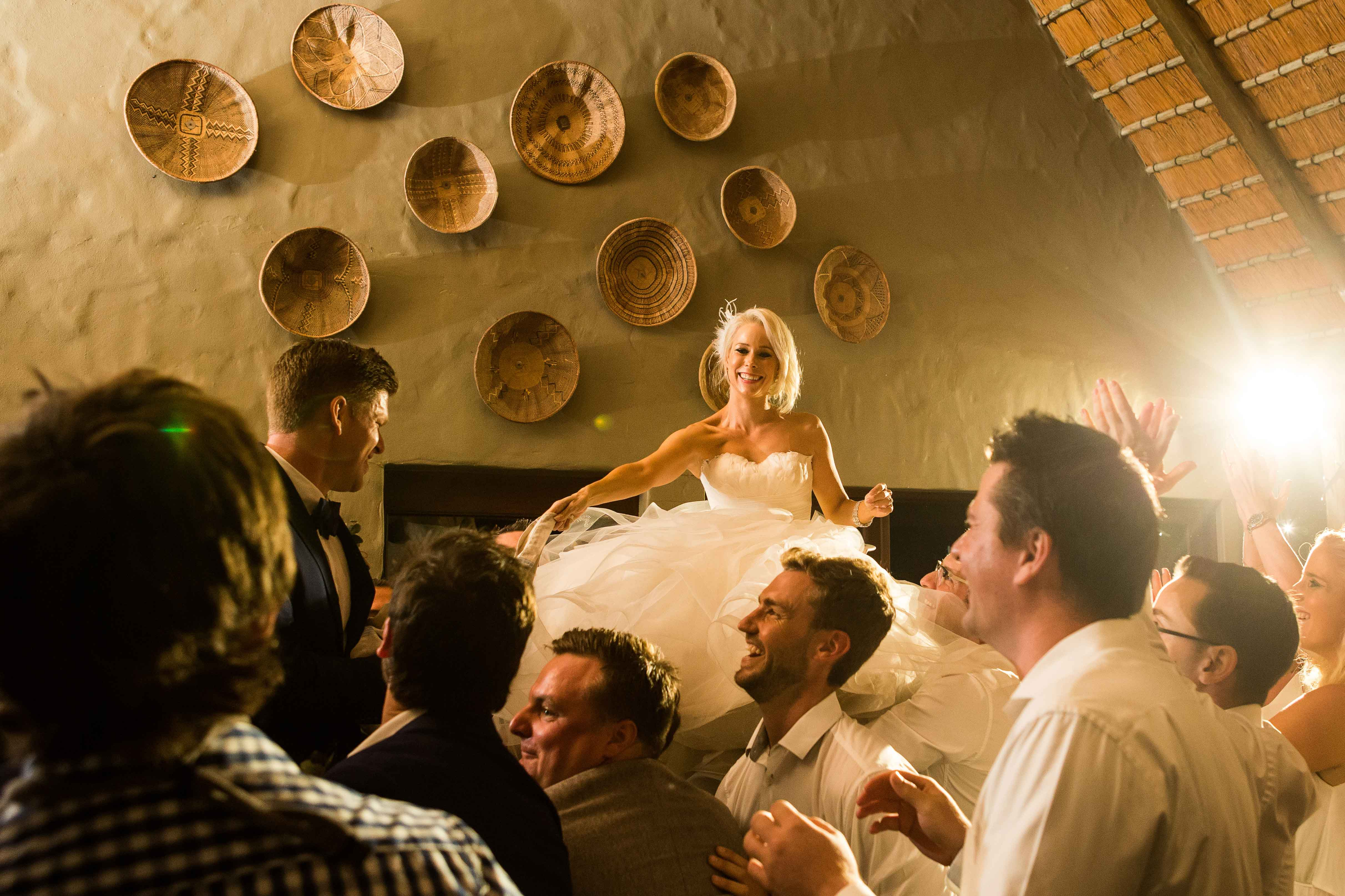 Bride and groom lifted in chairs doing hora at private game reserve South Africa