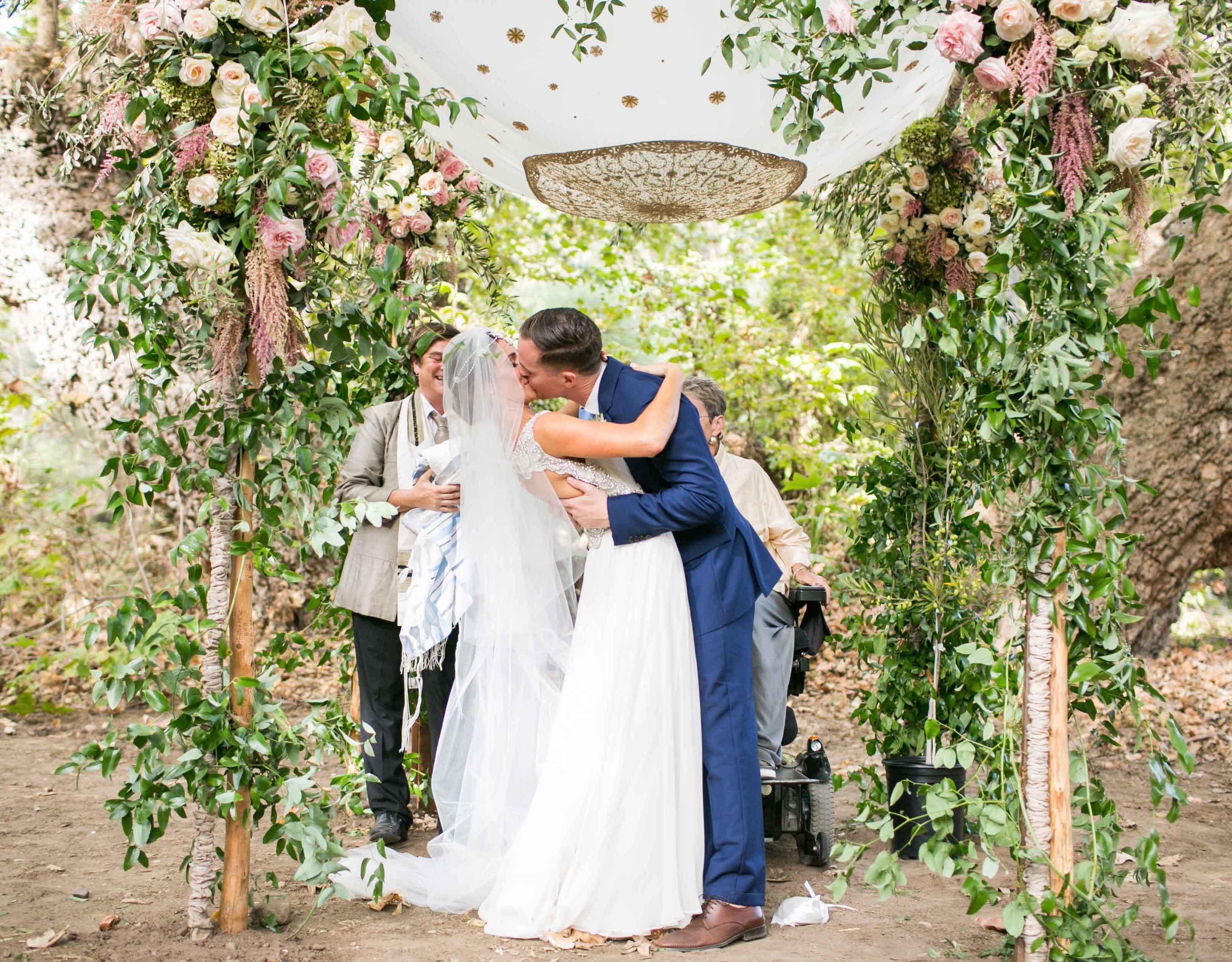 Bride with veil kissing groom on foliage swing Dear Maradee Wahl styling