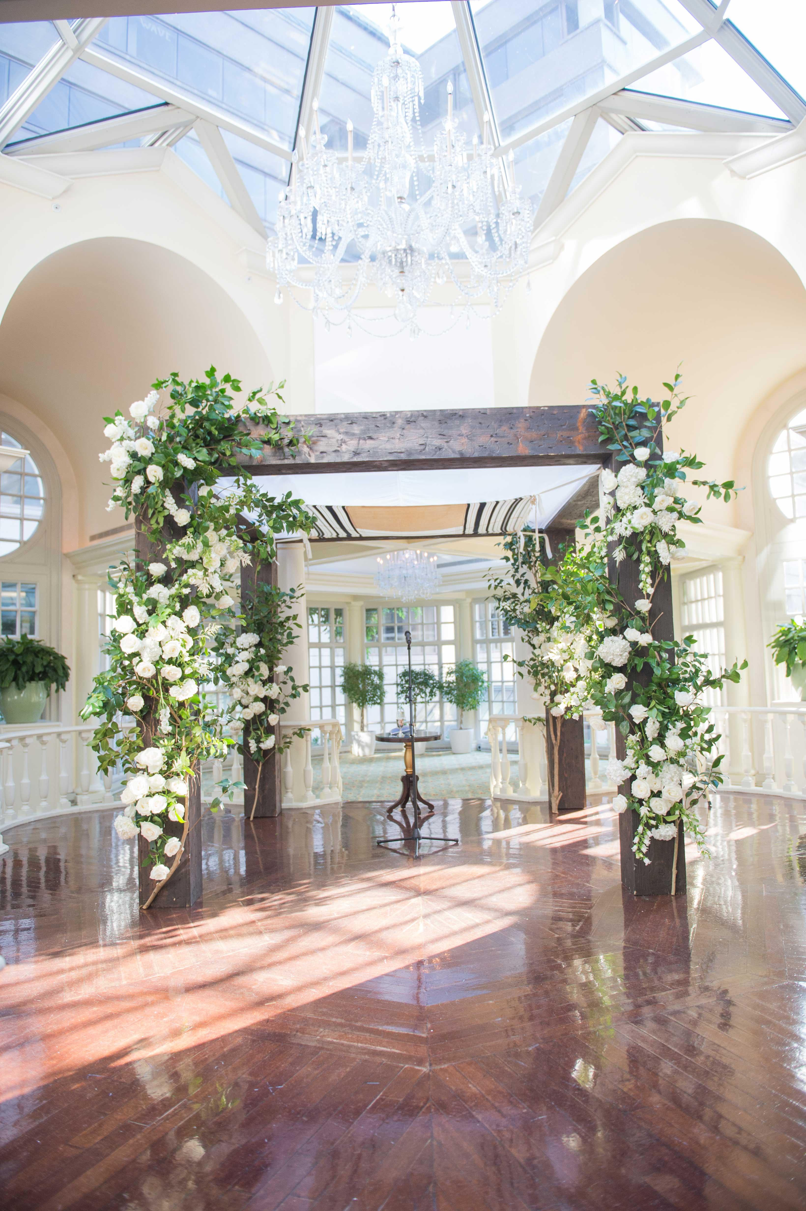 large chuppah made of wooden columns on hardwood floor for indoor wedding