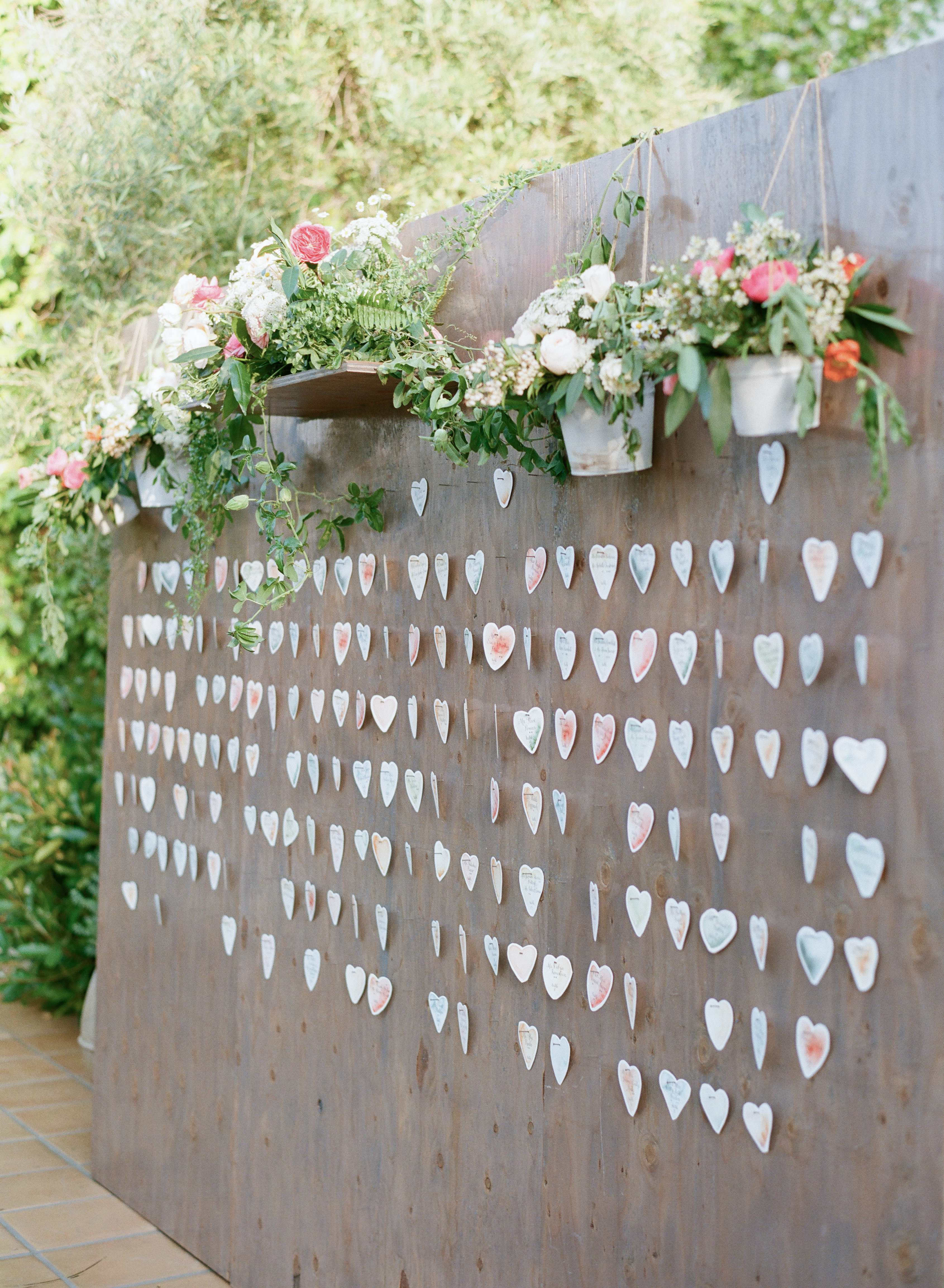 large wooden wall with paper hearts for guest escort cards
