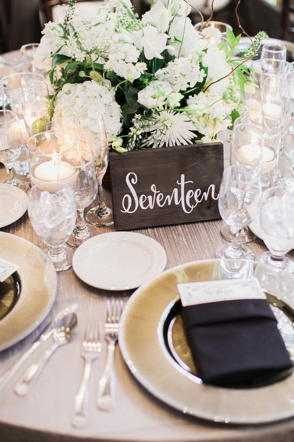 wedding reception table with table number written out with white calligraphy on wooden slab