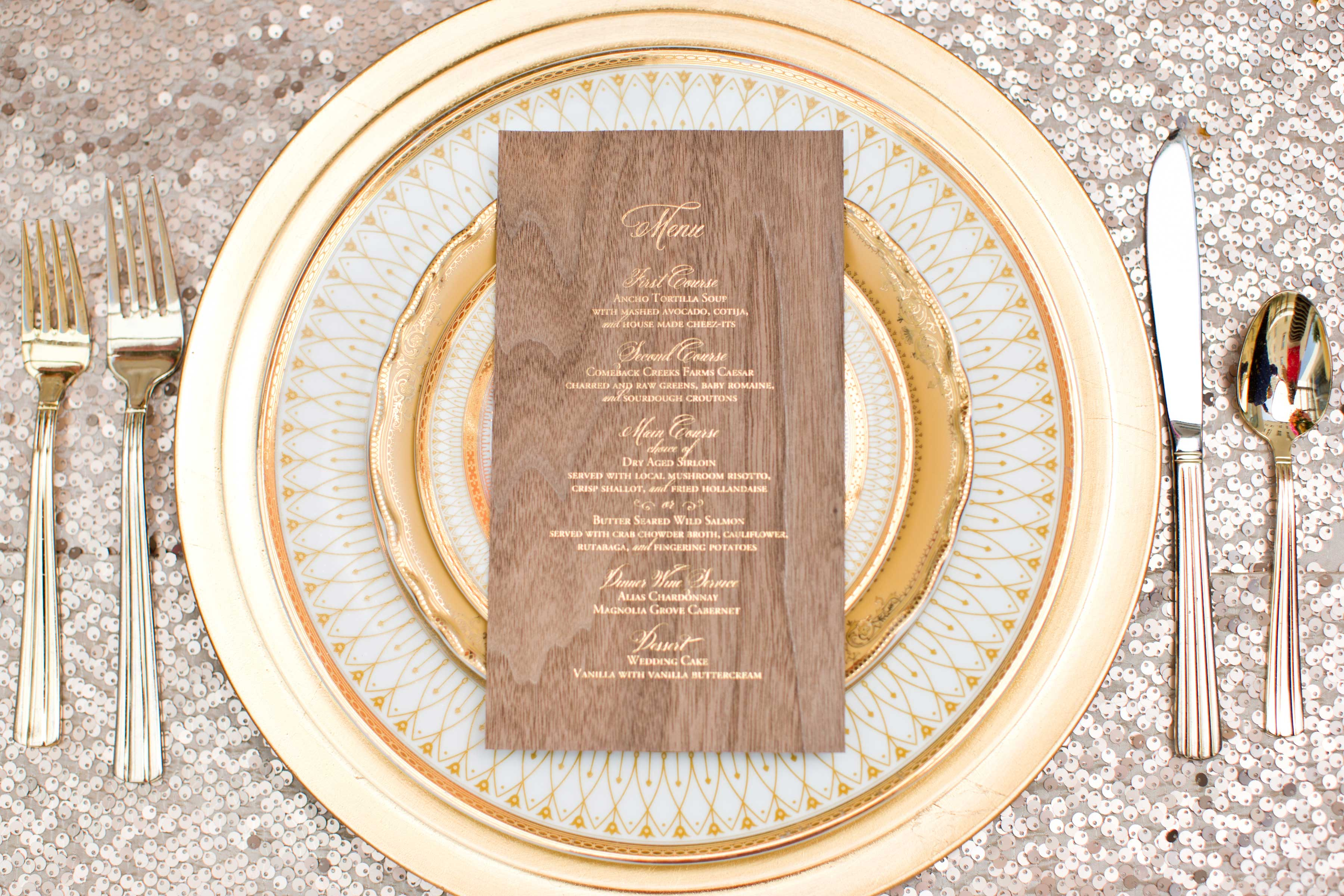 gold sequin linens with gold detailed china for wedding place setting with thin wooden menu card