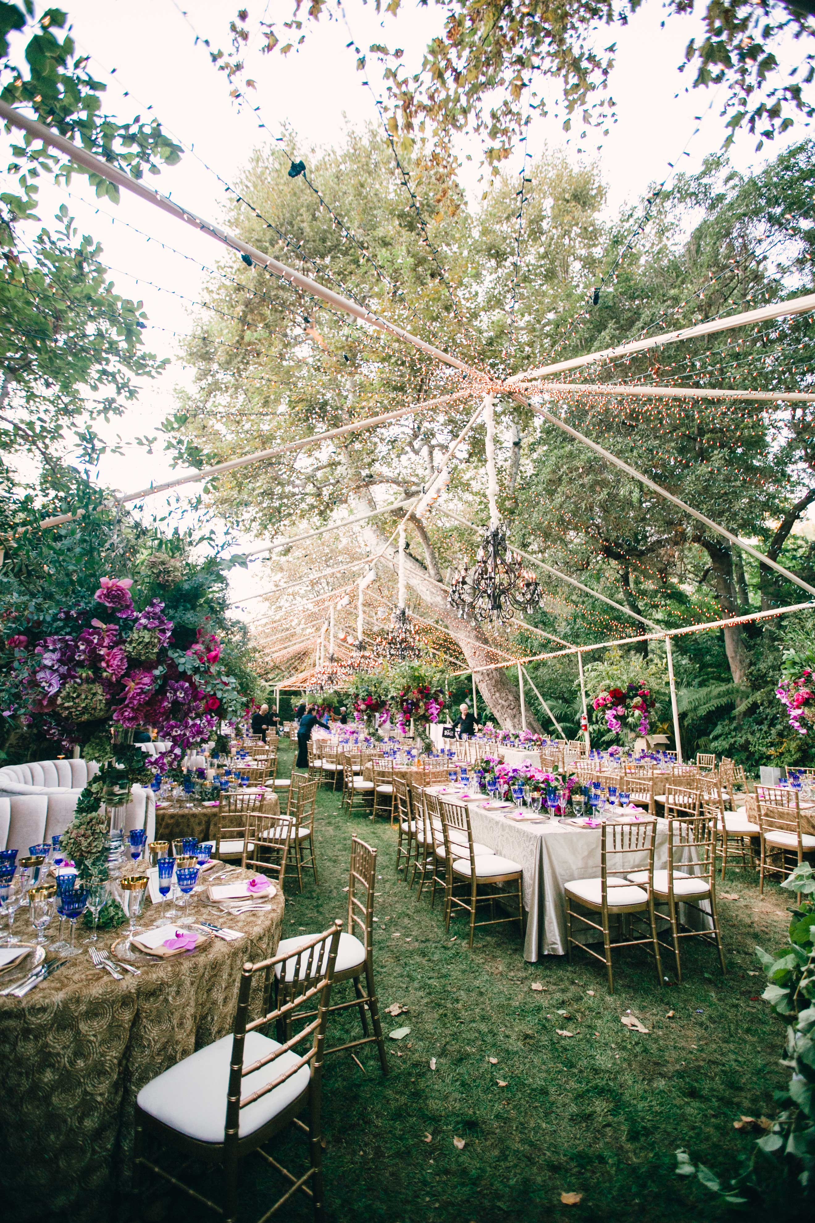 Outdoor colorful wedding reception under clear top tent with twinkle lights