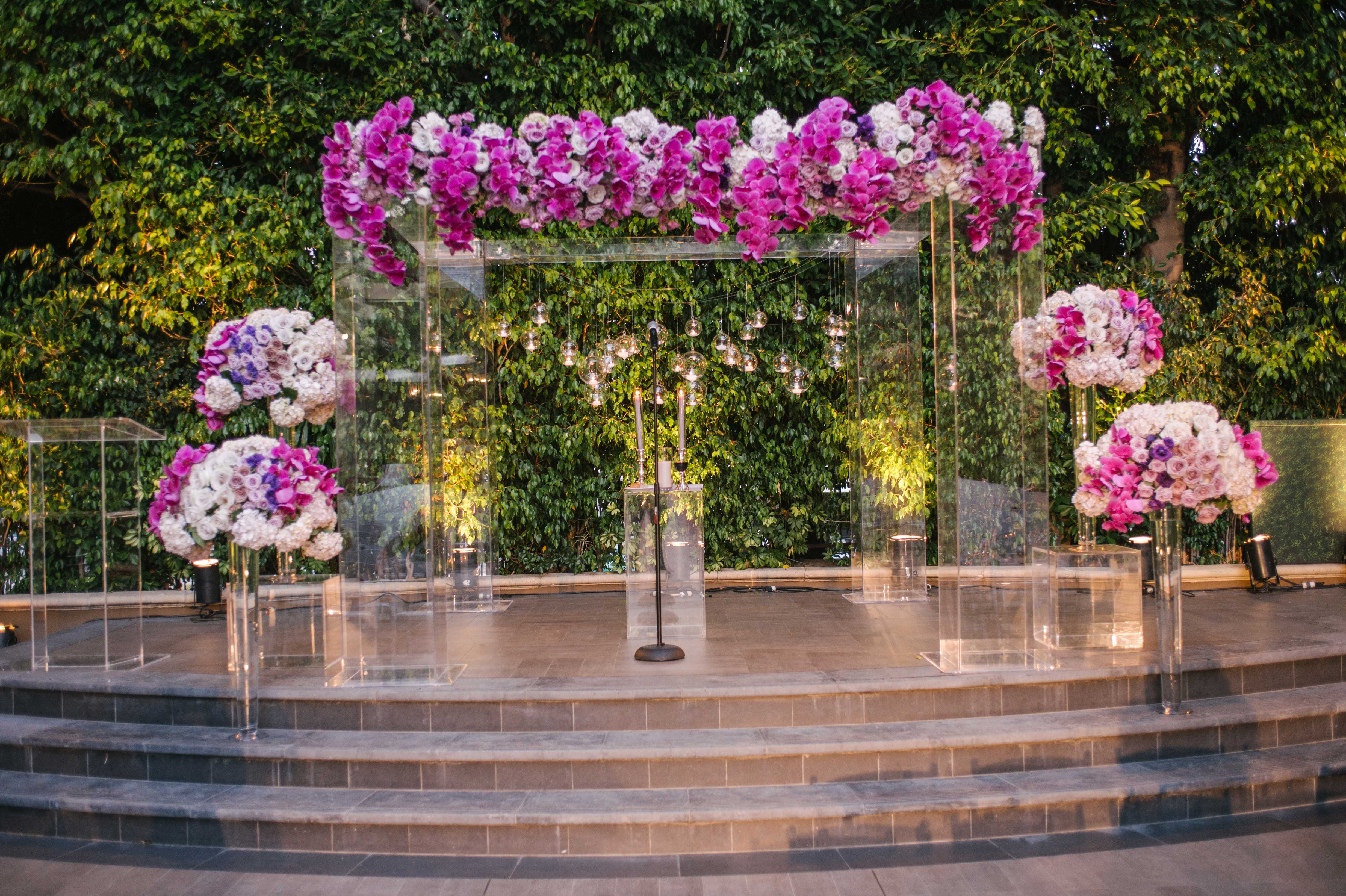 Clear lucite ceremony structure arch with purple flowers color palette