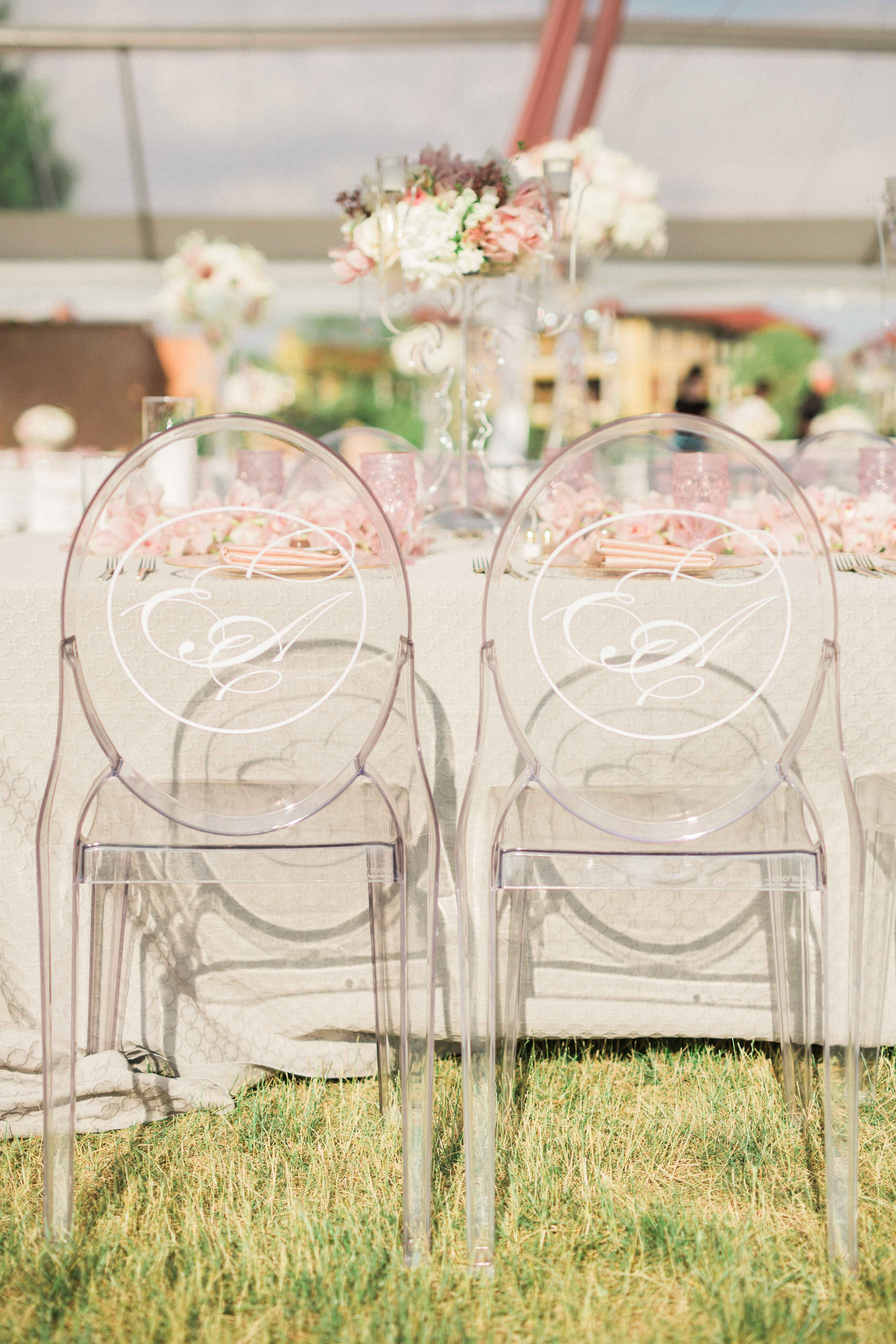 Clear ghost chairs at outdoor ceremony with white monogram on back