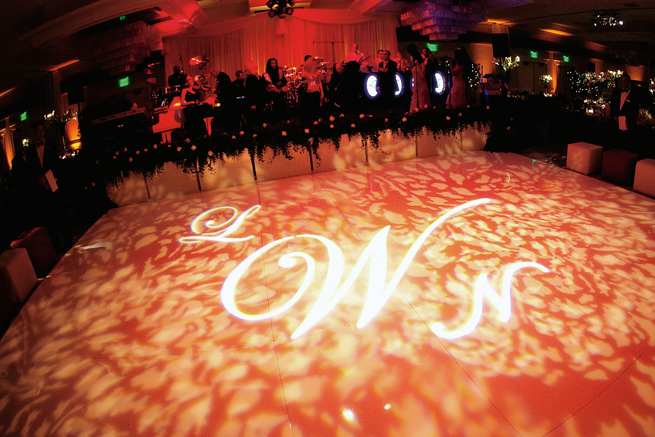 light projection of leaf pattern and monogram on dance floor at wedding reception