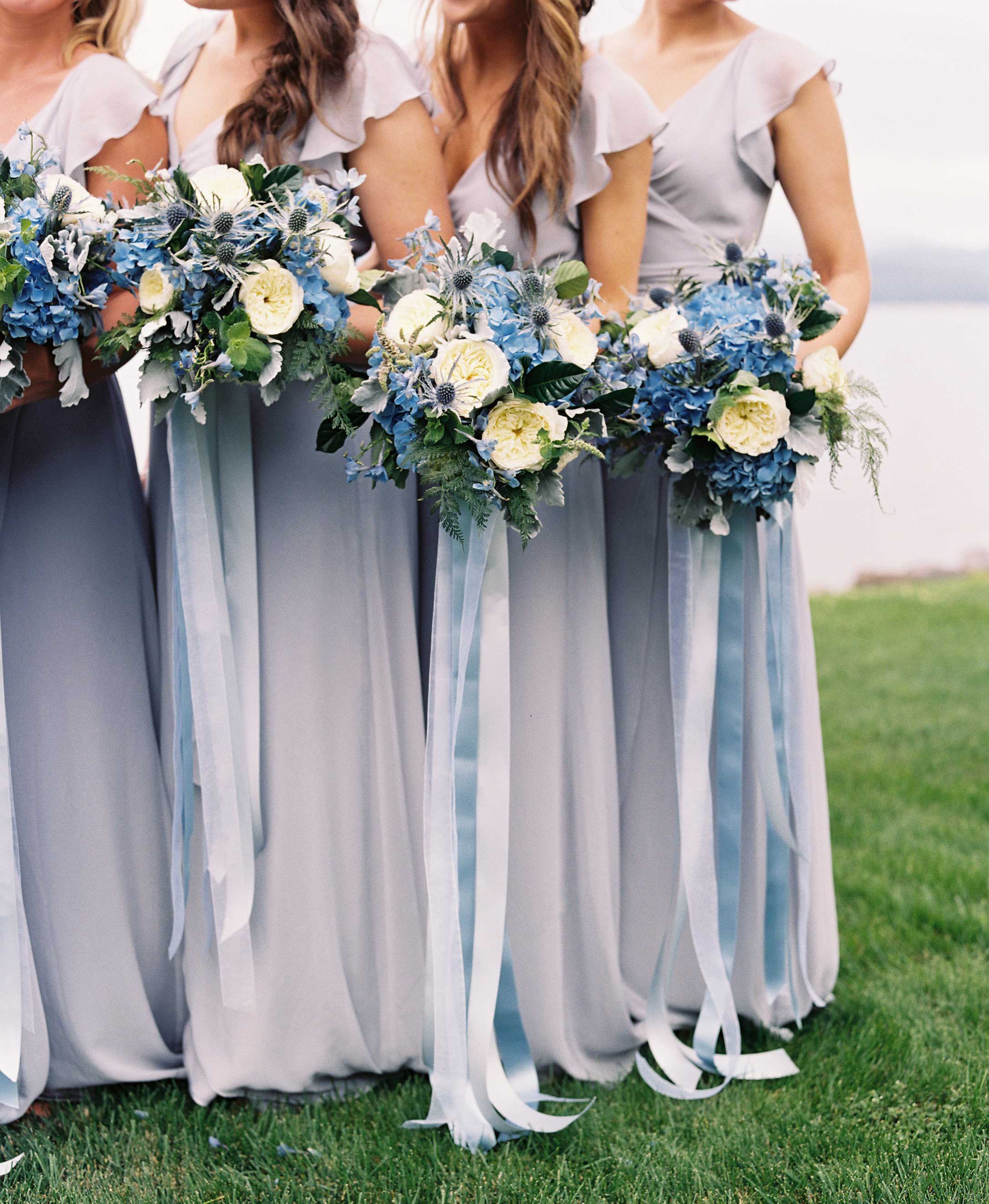Bridesmaids in long Joanna August blue-grey dresses with blue bouquets and ribbons