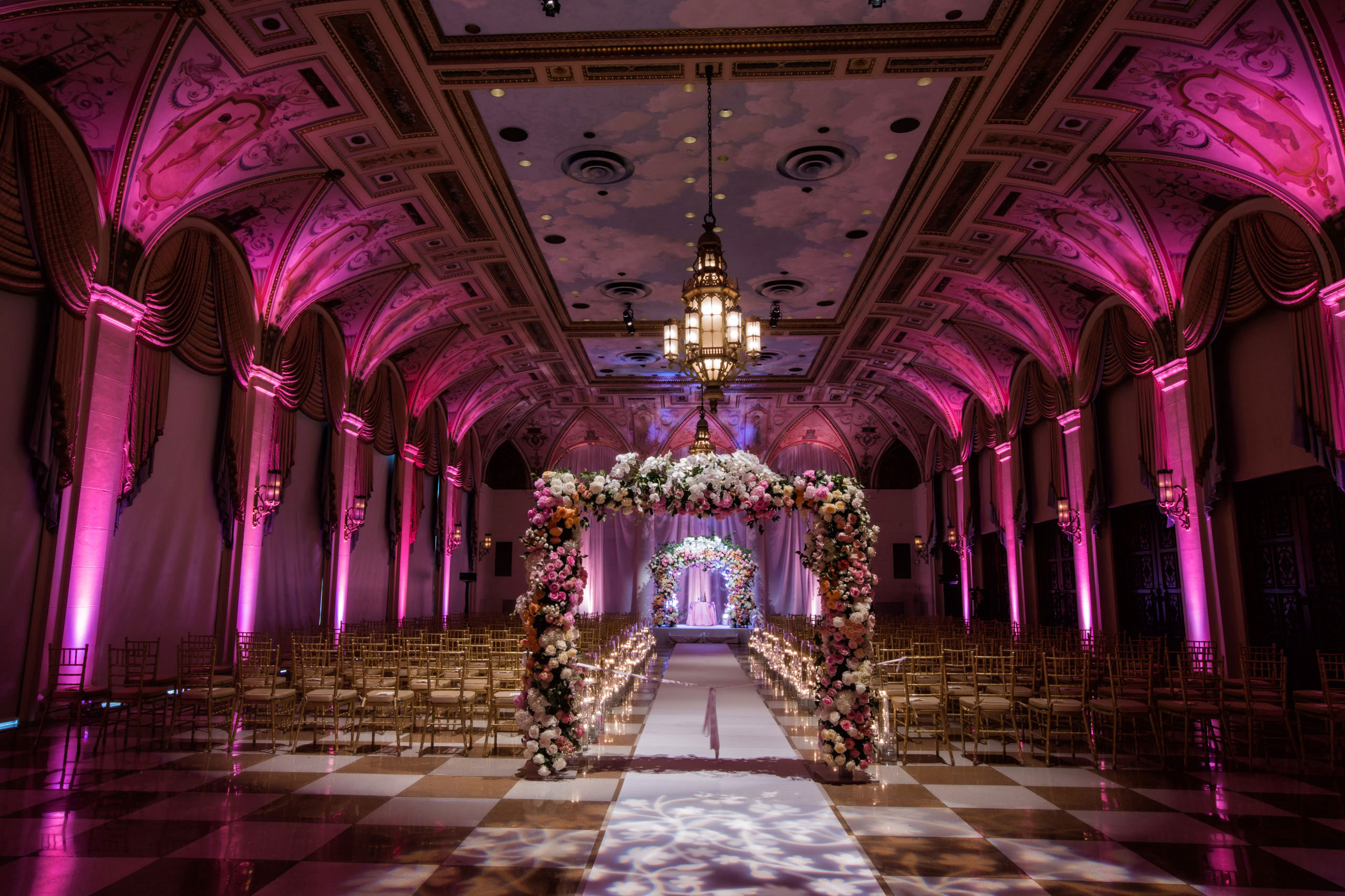 Dark and moody color palette wedding ceremony fuchsia lighting checkered ballroom floor The Breakers