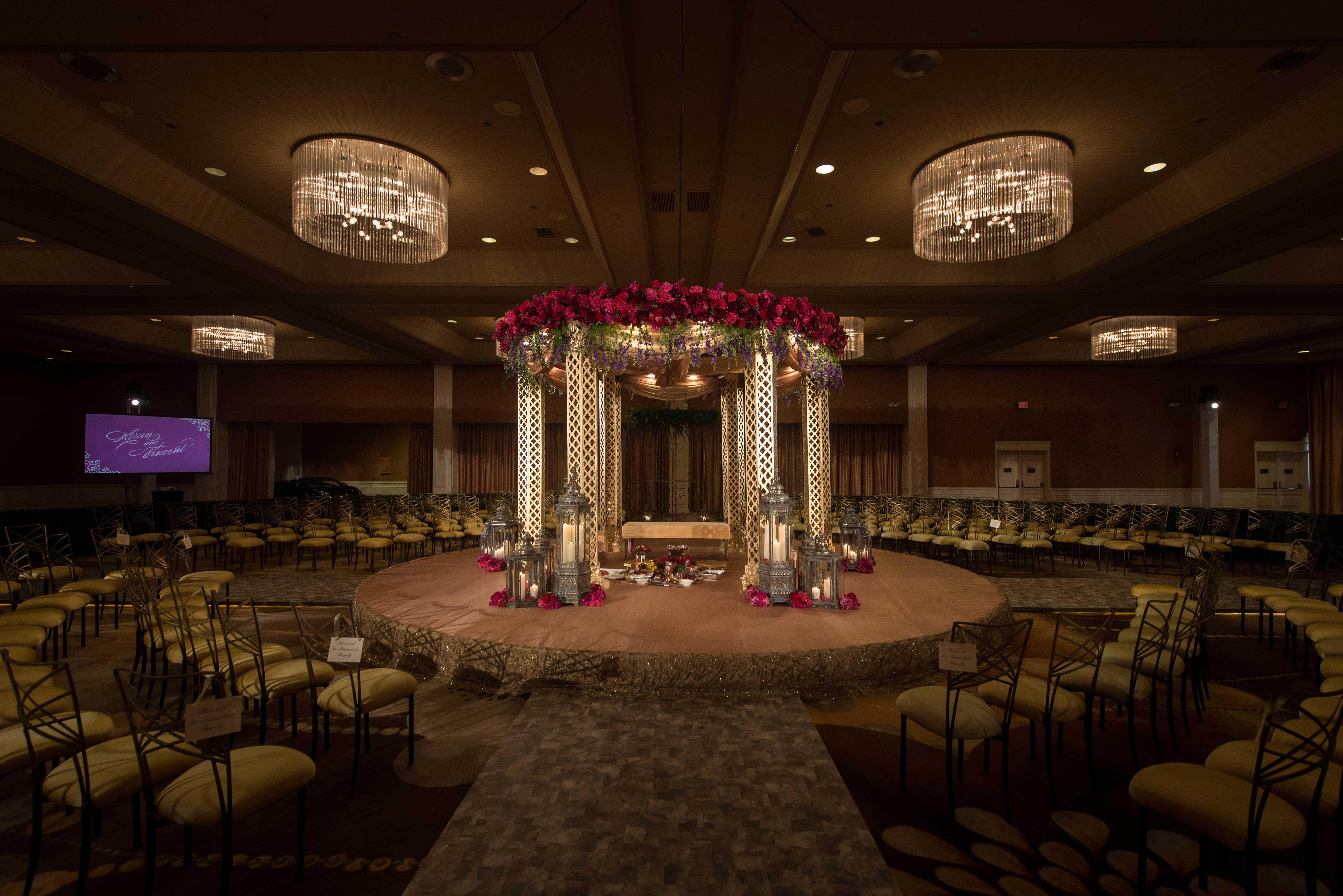 Dark and moody interfaith Indian Catholic wedding ceremony in ballroom