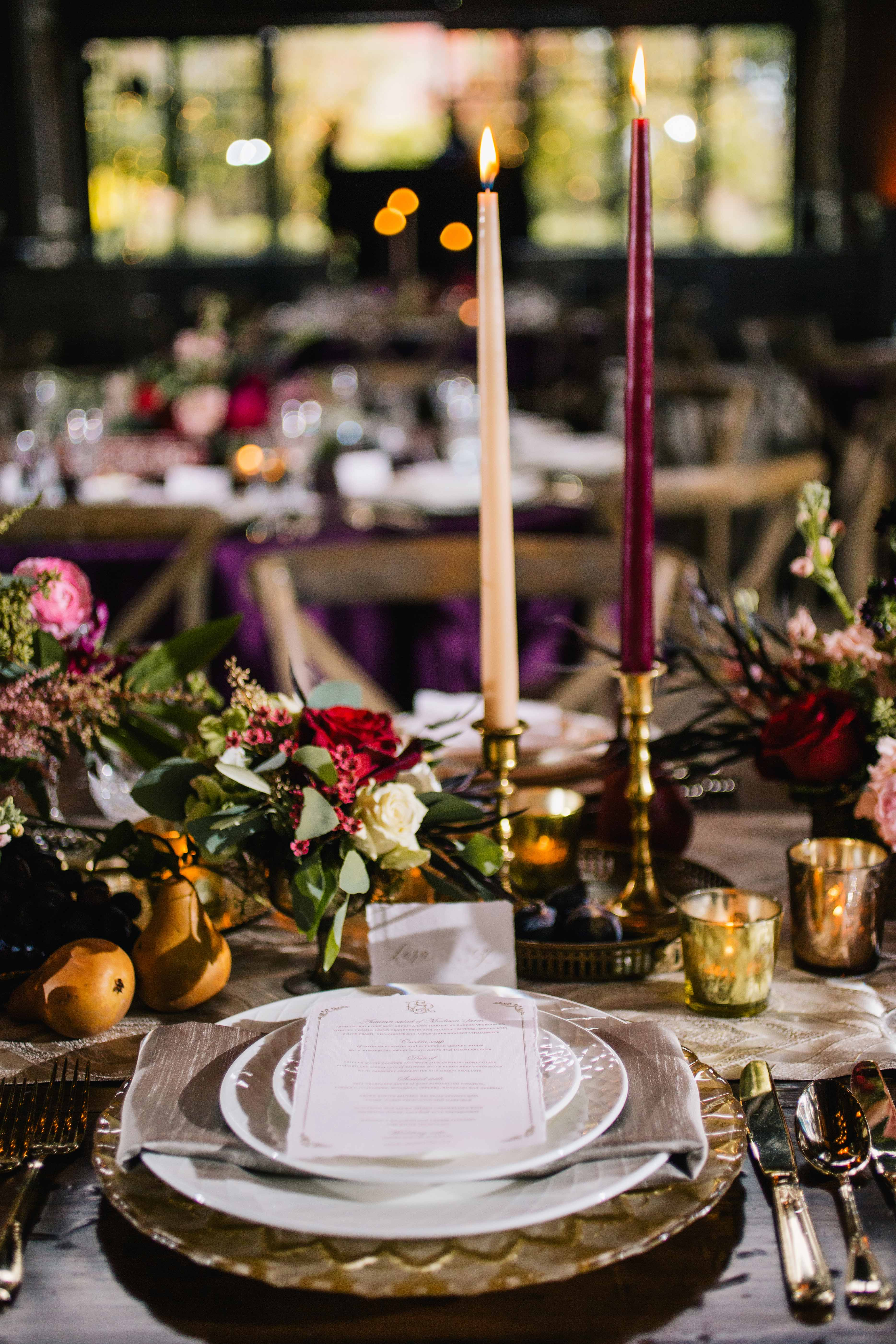 Dark and moody wedding reception place setting with tall taper candles