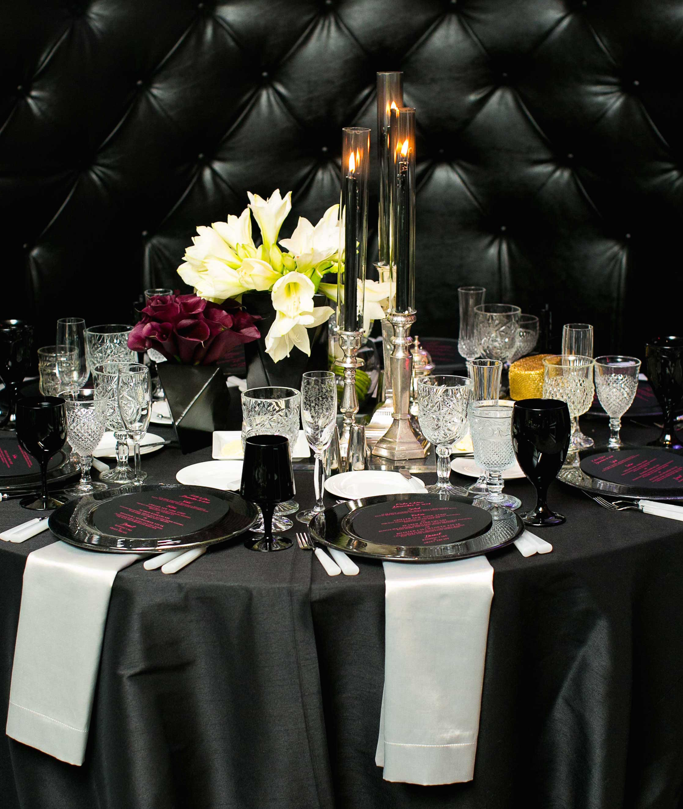 Black tufted settee with black table dark and moody wedding color palette reception ideas