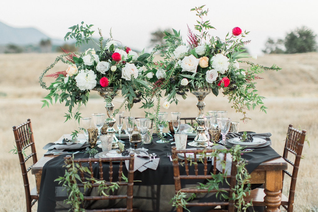 Dark and moody wedding color palette ideas black table linen and dark red flowers with greenery