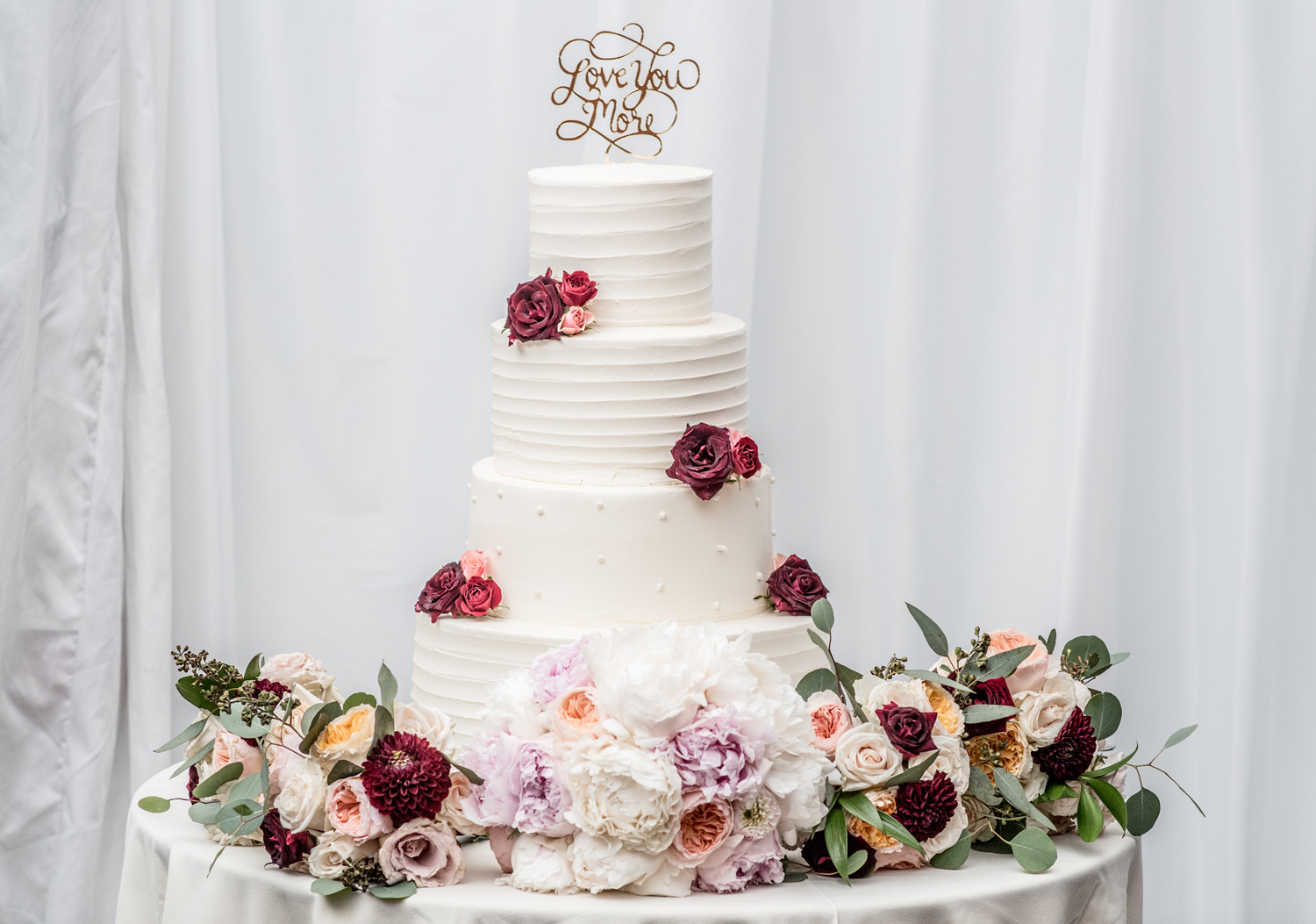White wedding cake with dark and moody color palette fresh flower decorations