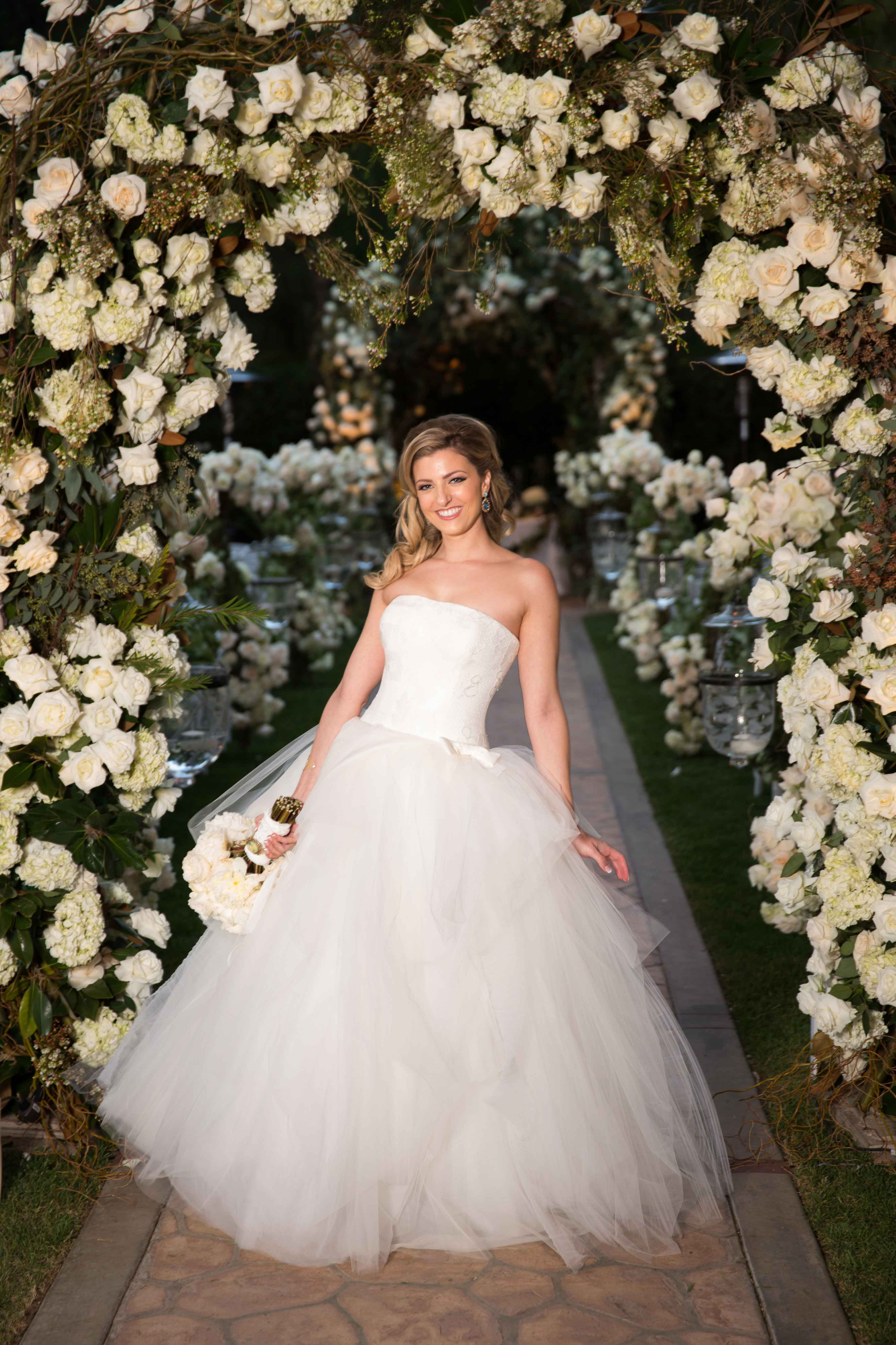 bride in vera wang strapless tulle ball gown holding bouquet off to the side, shows off dress