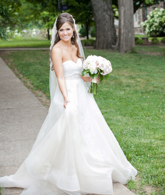 bride holds bouquet off to the side, holds skirt in rivini wedding dress