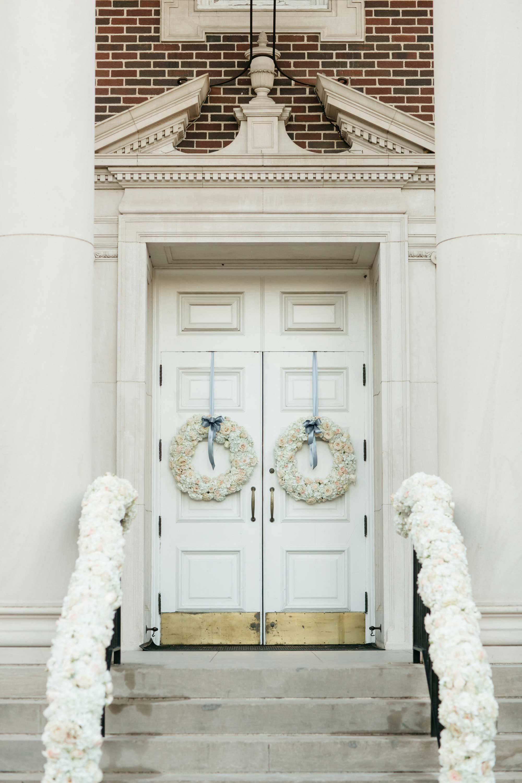 White flower wreaths hanging on church doors with blue ribbon