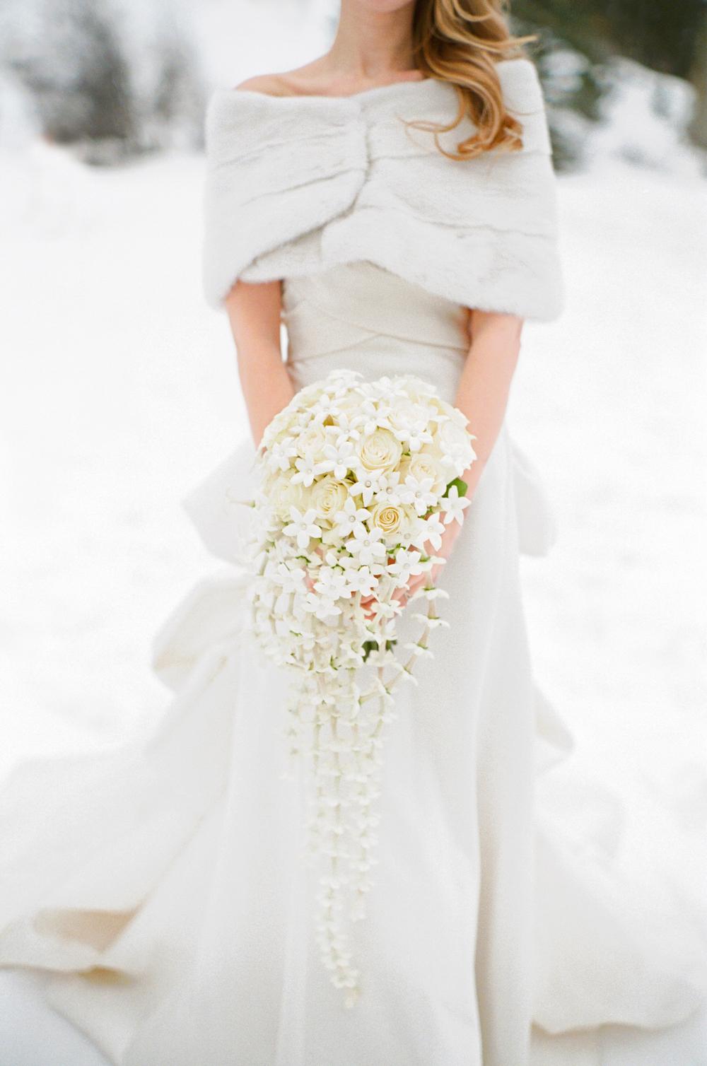 Bride in snow white dress fur bolero cascading white winter wedding bouquet
