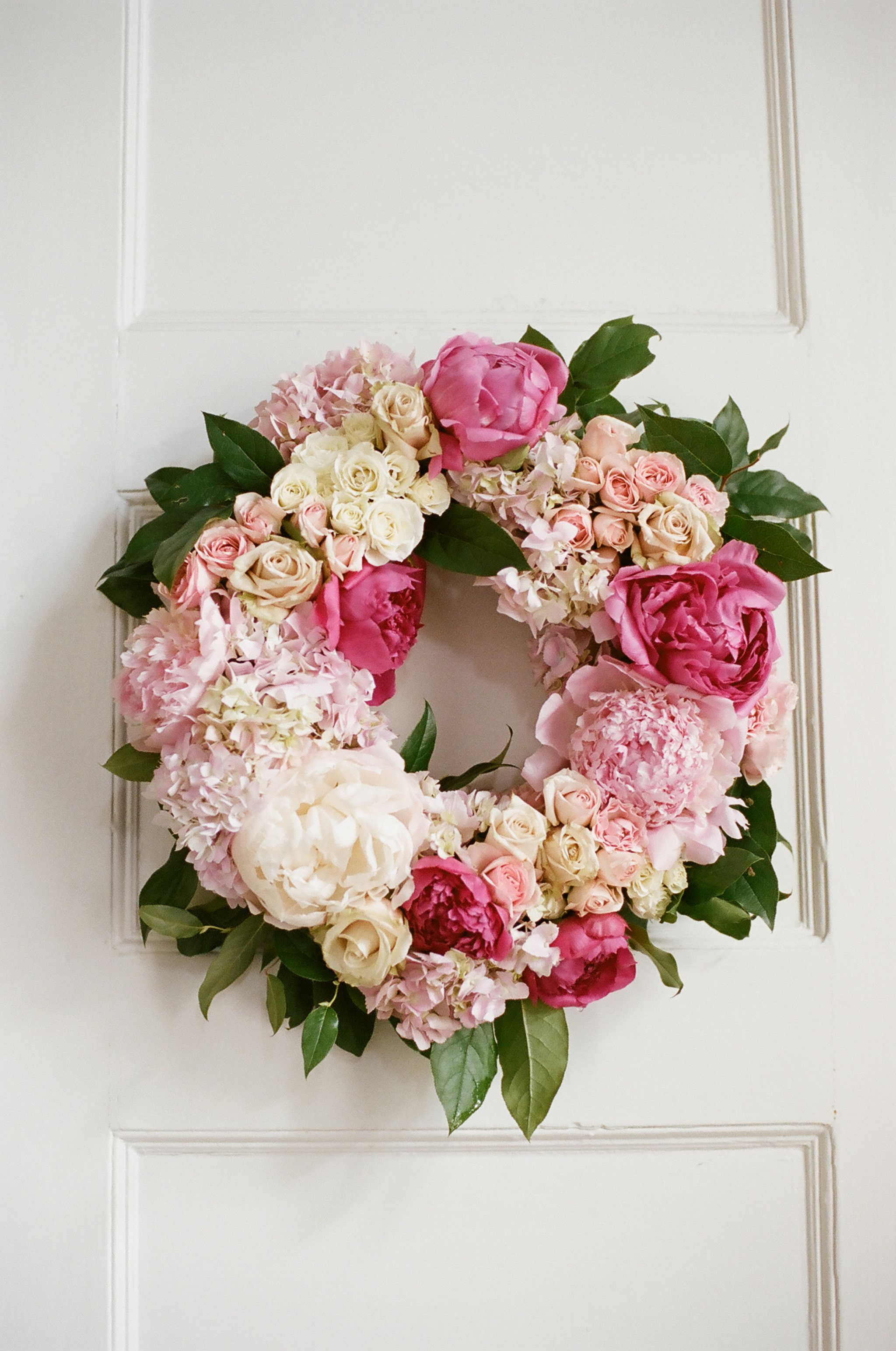 White and pink wreath on church door with greenery peony and rose flowers