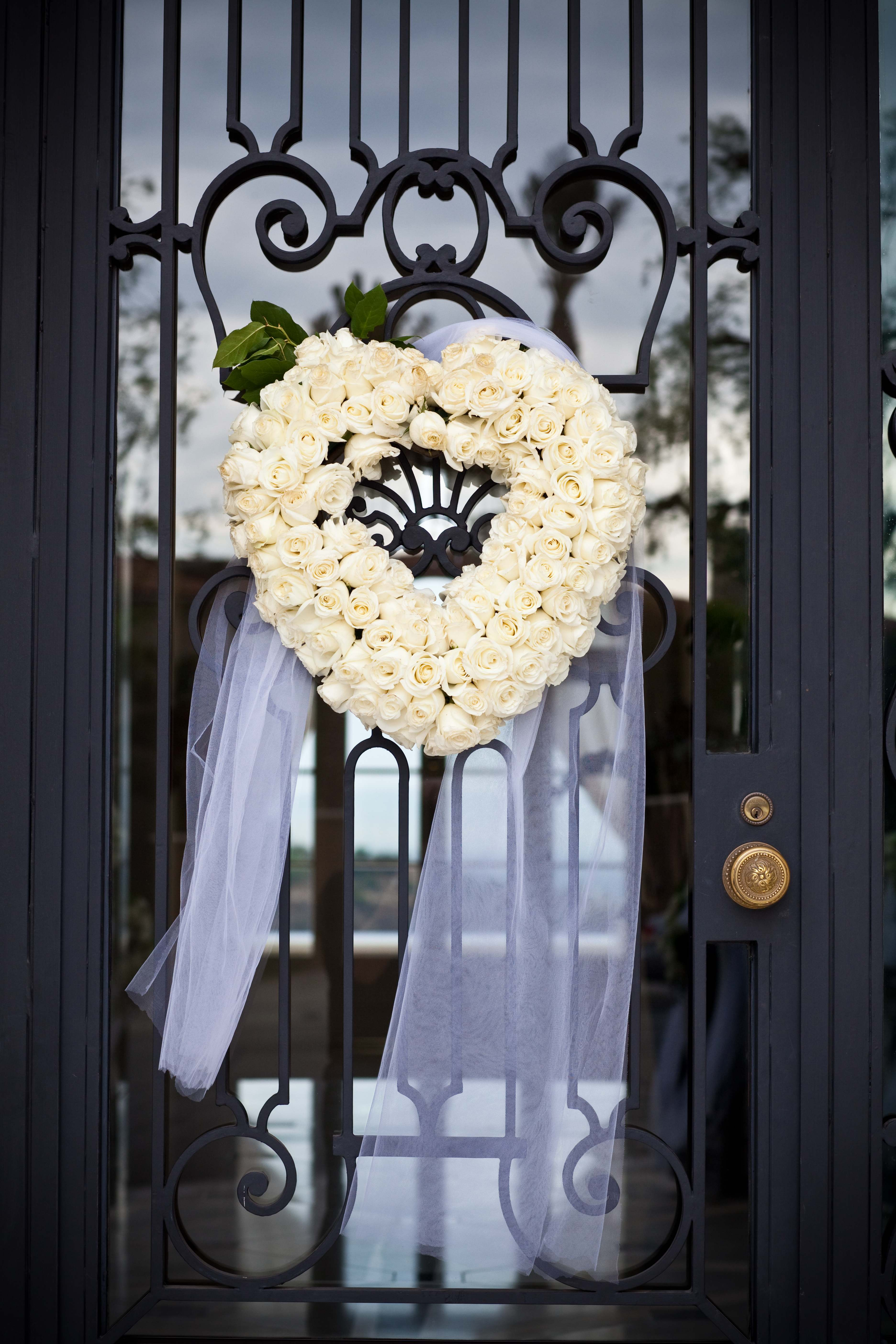 White rose heart shape wreath on iron gate for wedding